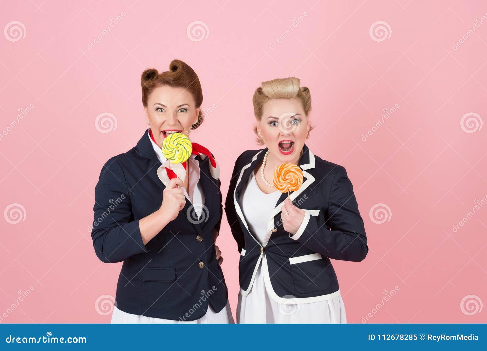 Pares doces de meninas com pirulitos O Pin-acima denominou mulheres com doces à disposição Duas senhoras doces com dois doces