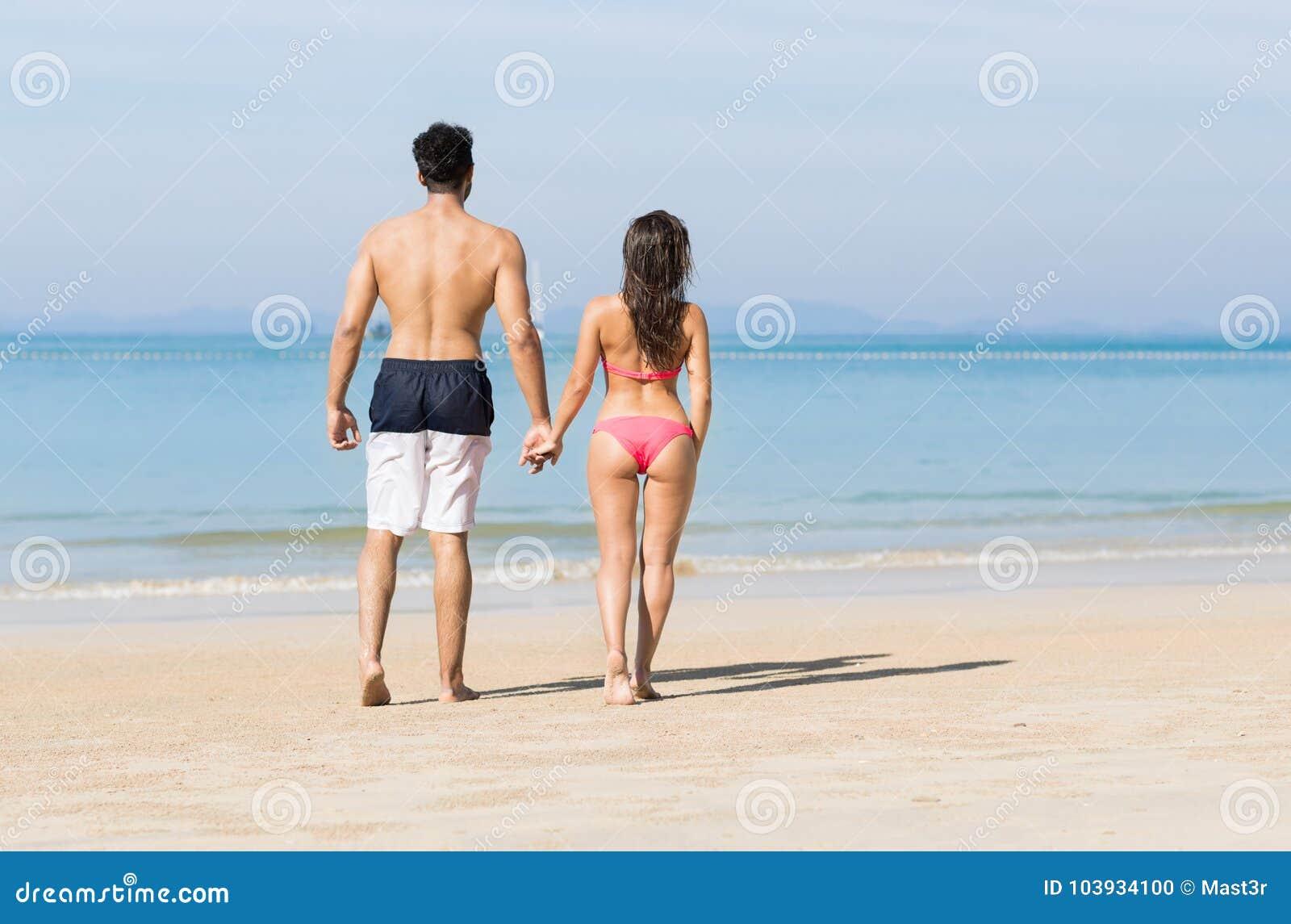Pares el vacaciones de verano de la playa, gente joven en amor que camina, mujer del hombre que sostiene el océano del mar de las