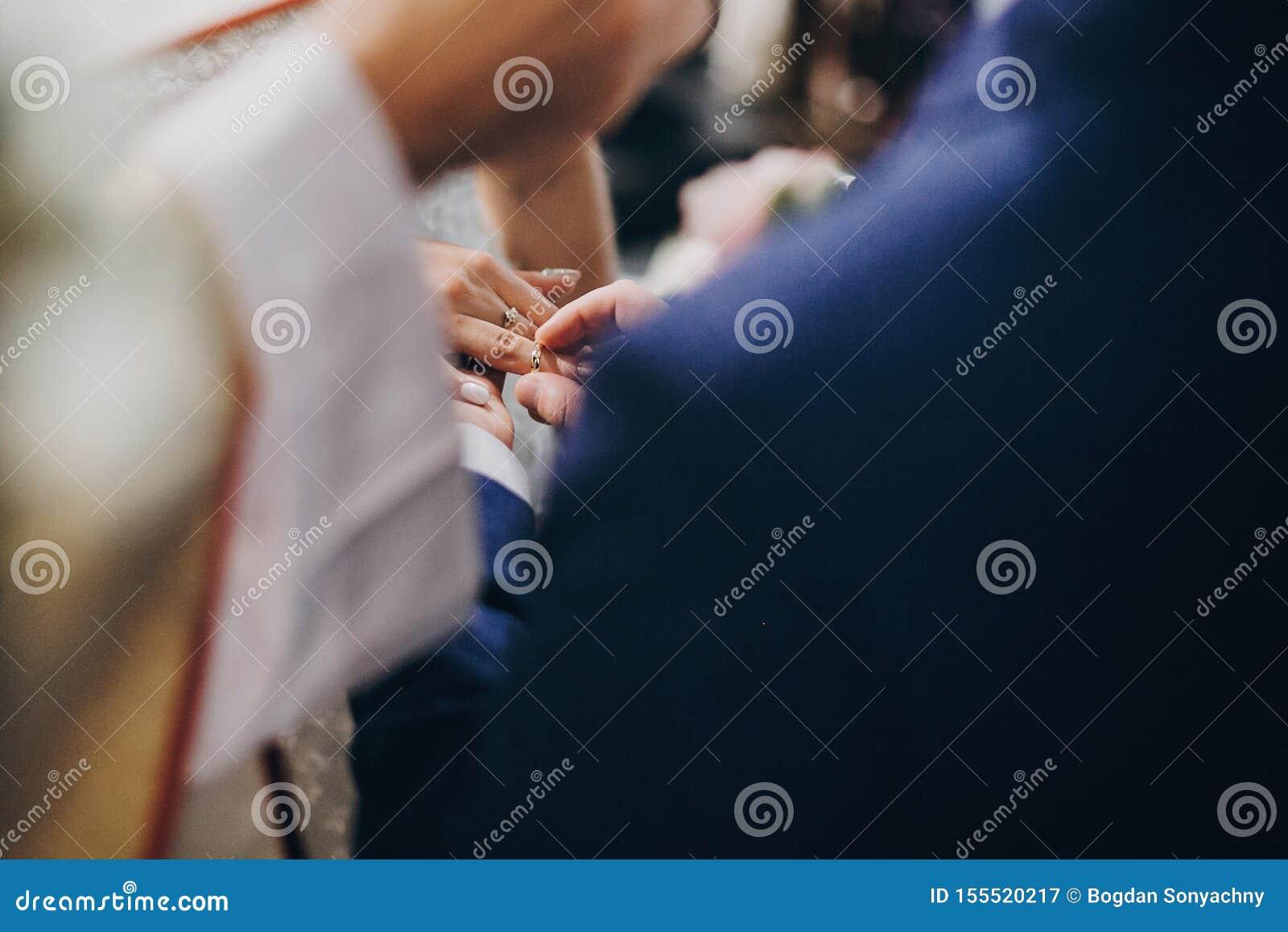 Pares elegantes de la boda que intercambian los anillos de bodas en el matrimonio santo en iglesia Opinión cosechada la novia y e