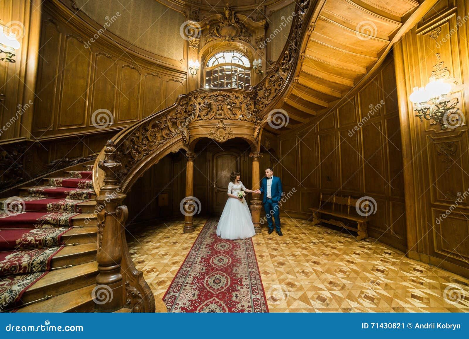 pares elegantes de la boda que se colocan en la casa y el palacio viejos del