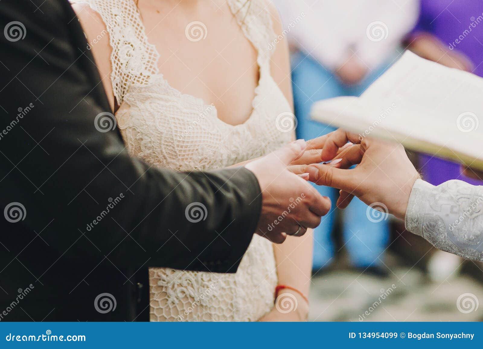 Pares elegantes felices de la boda que intercambian los anillos de bodas durante matrimonio santo en iglesia Novia y novio que po