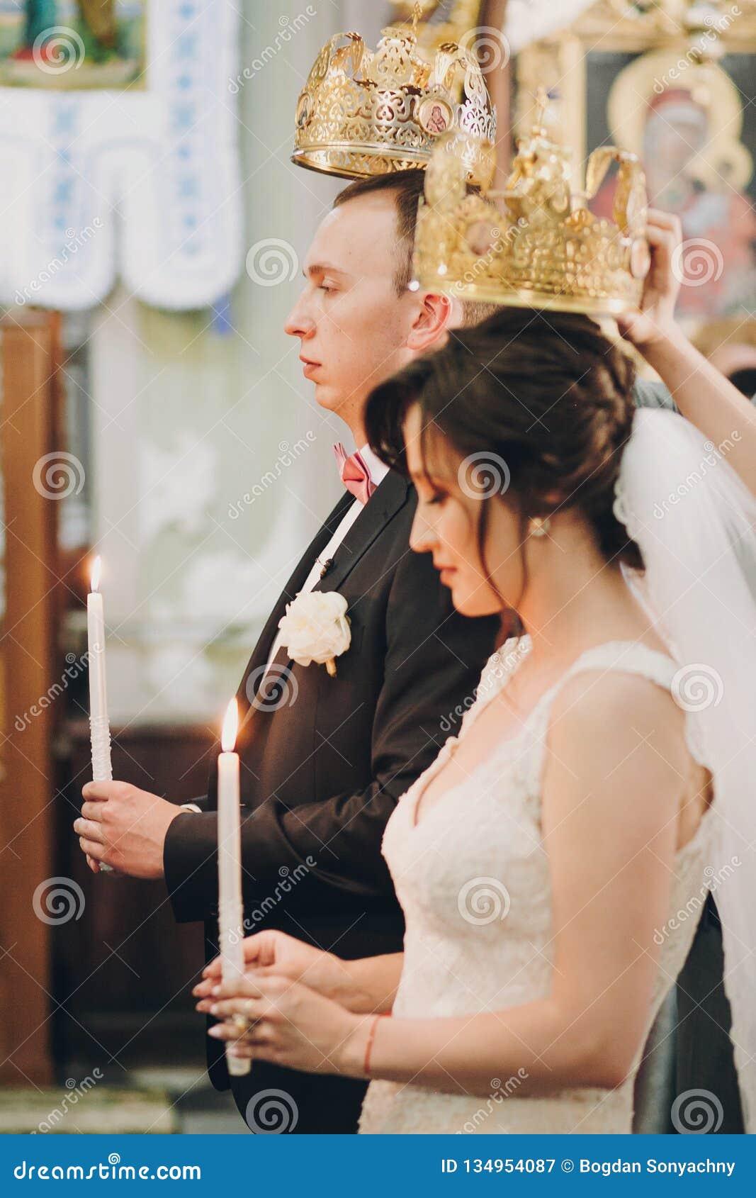 Pares elegantes felices de la boda que llevan a cabo velas con la luz debajo de las coronas de oro durante matrimonio santo en ig