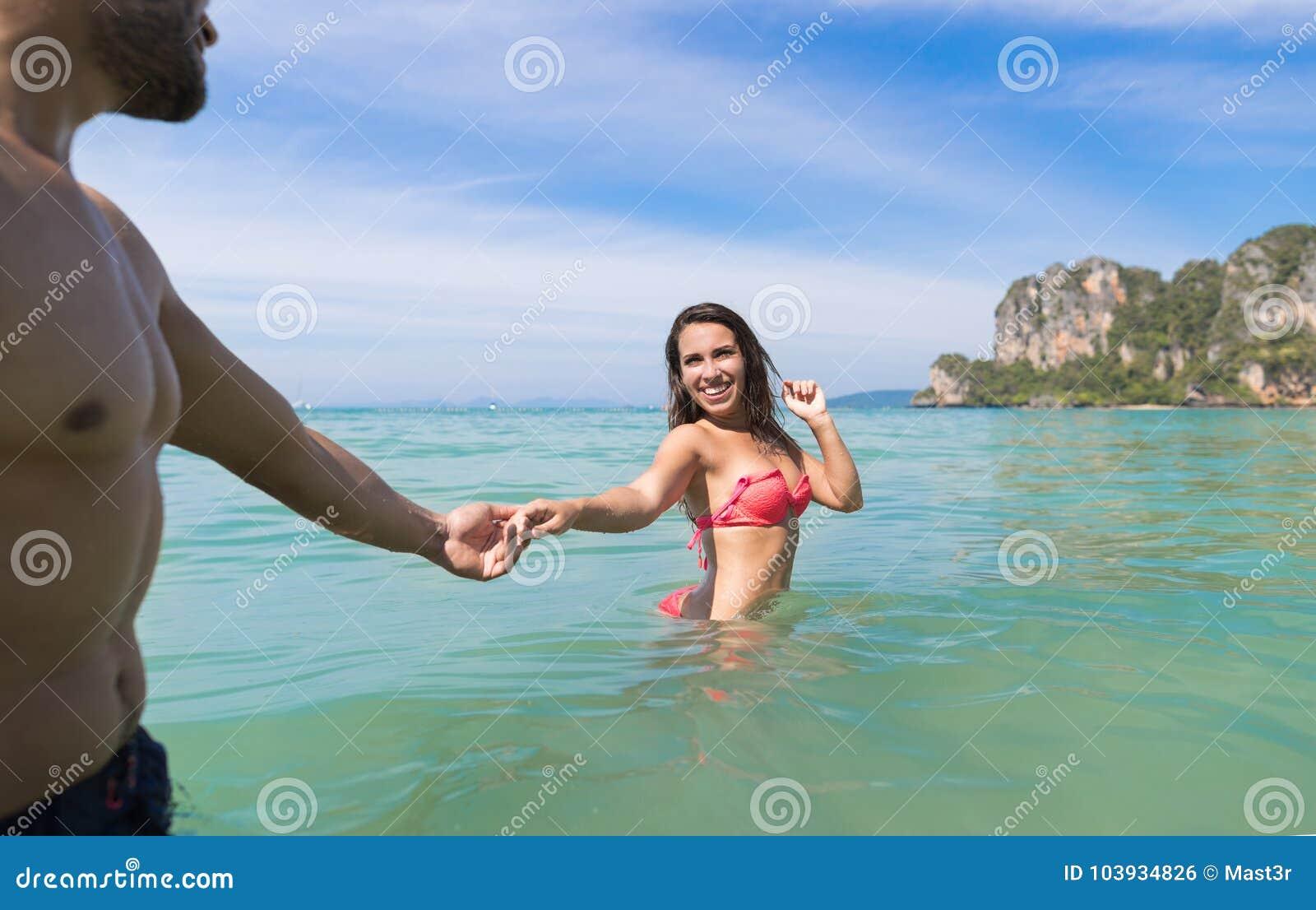 30bcf3ac6 Pares em férias de verão da praia, jovens na água, mulher que guarda o  curso do feriado do oceano do mar da mão do homem