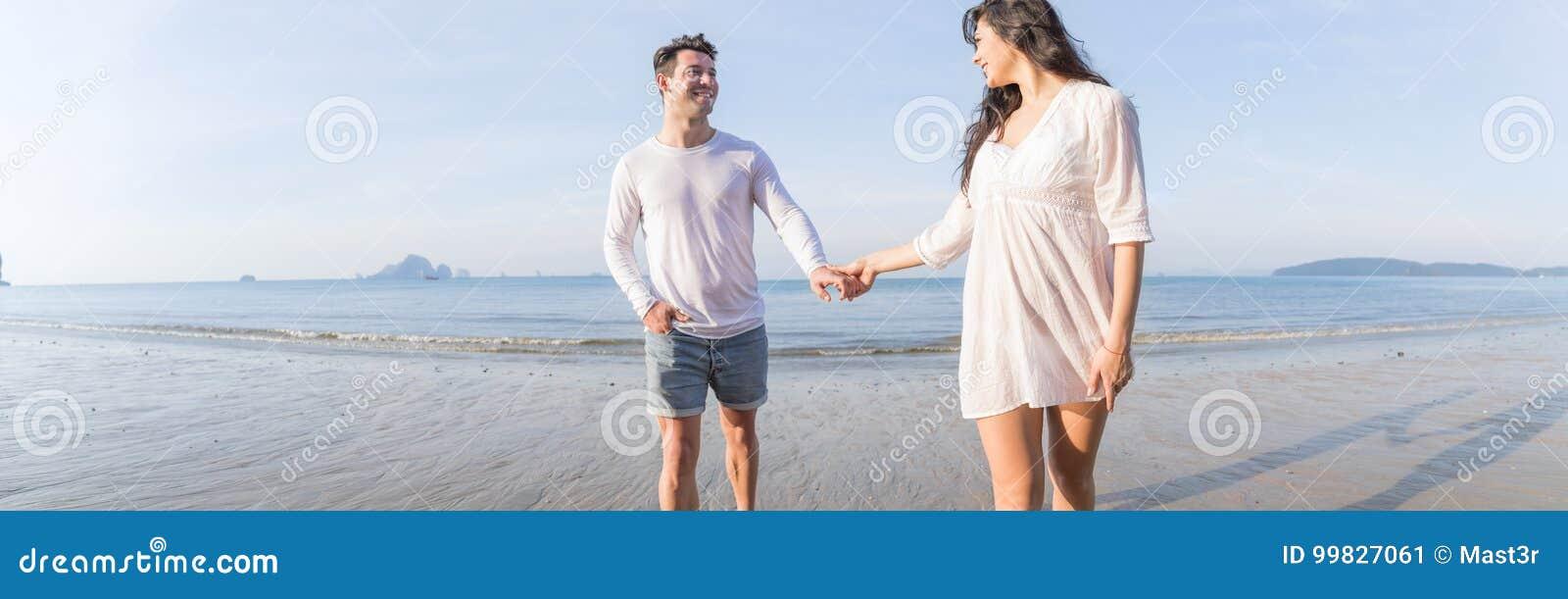 Pares em férias de verão da praia, povos felizes novos bonitos no amor que andam, sorriso da mulher do homem que guarda as mãos