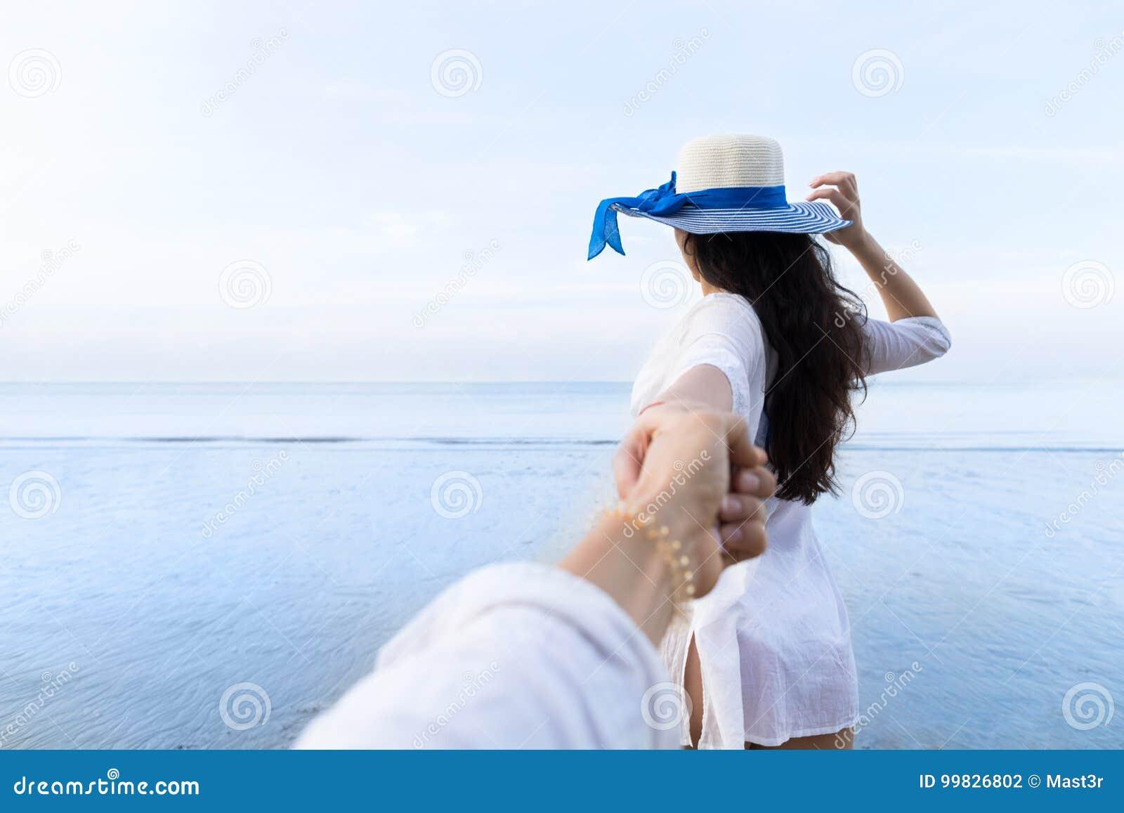 Pares em férias de verão da praia, povos masculinos da mão da posse bonita da moça que olham o mar