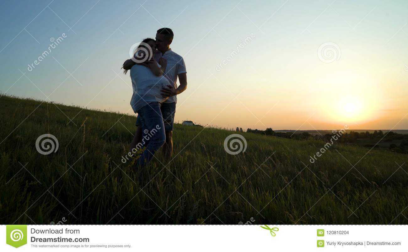 Pares embarazadas felices jovenes románticos que abrazan en naturaleza en la puesta del sol