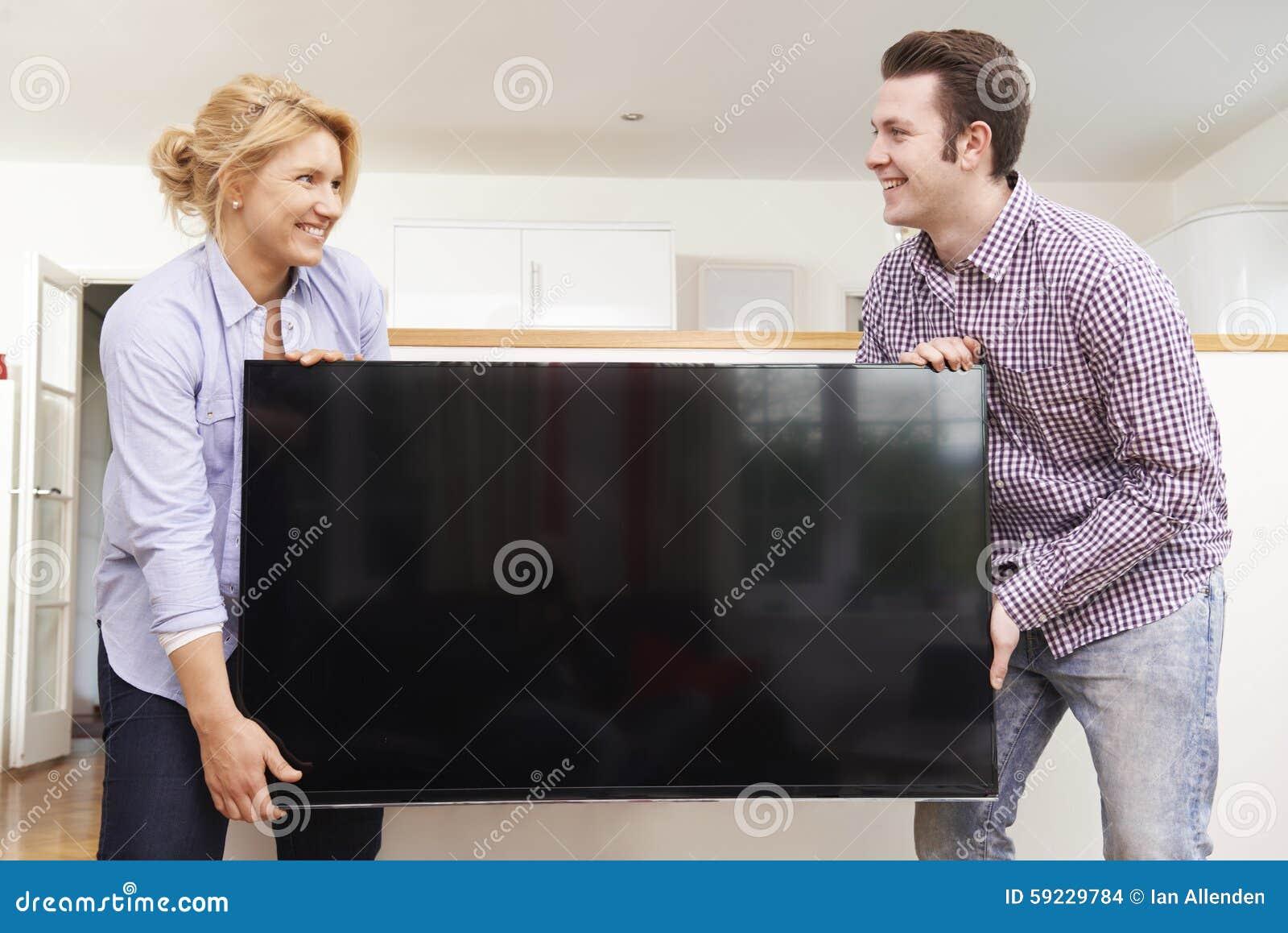 Pares emocionados que ponen la nueva televisión en casa
