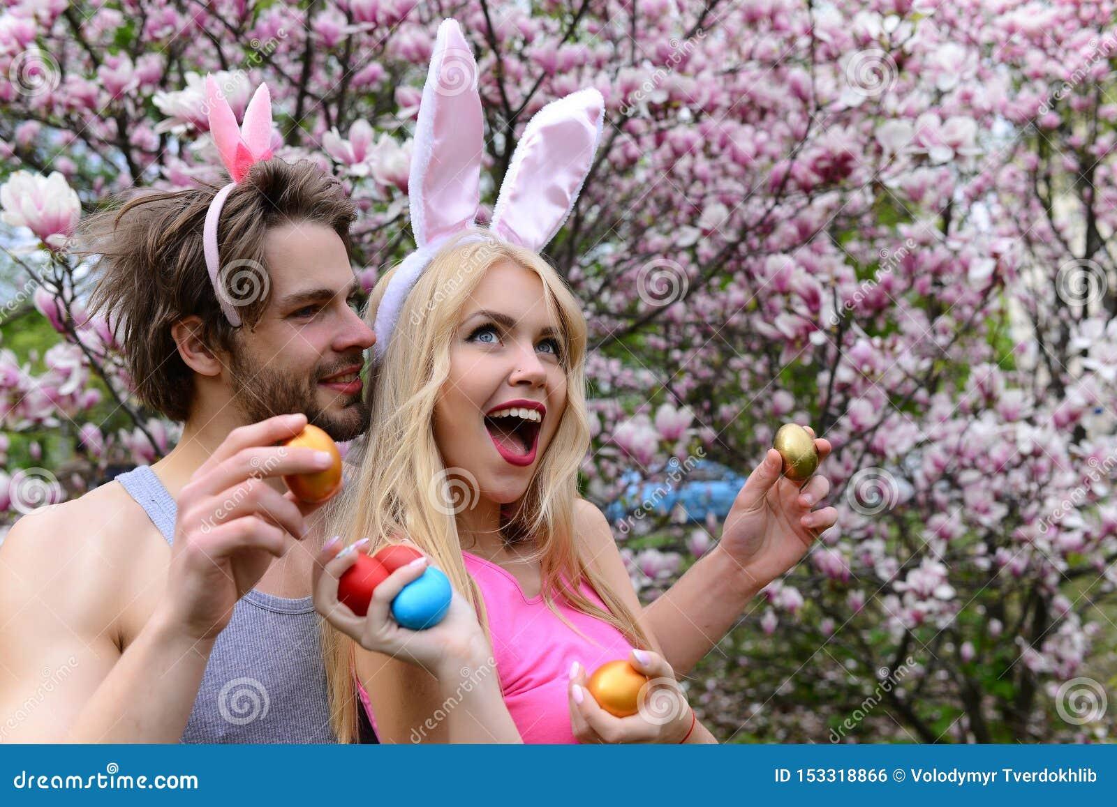Pares en amor con los o?dos del conejito que sostienen los huevos coloridos