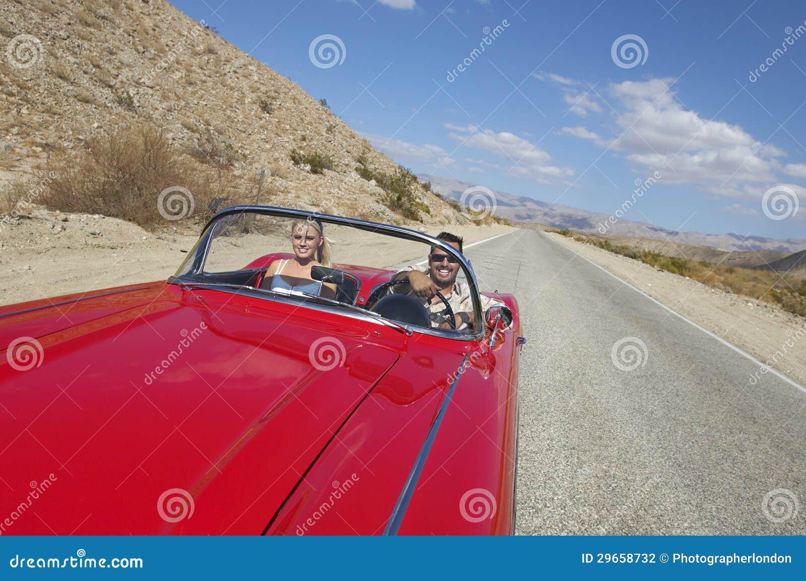 Pares en coche clásico en el camino del desierto