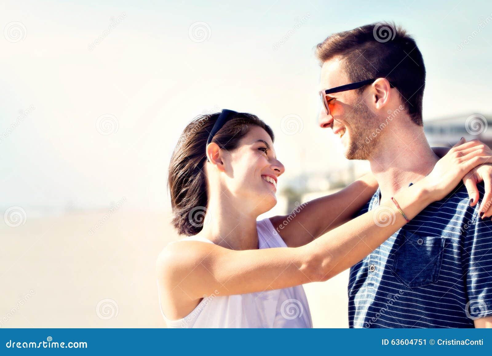 Pares en el amor que abraza cariñosamente delante del mar
