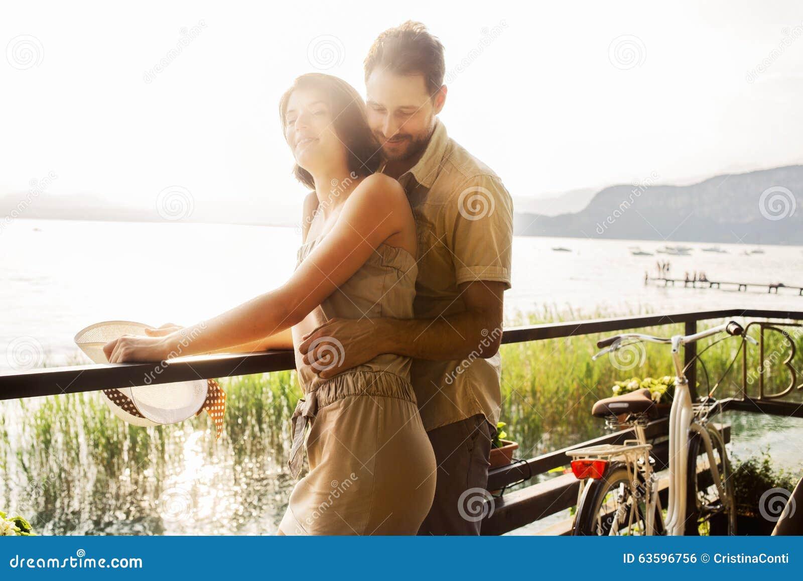 Pares en el amor que bromea en una terraza en el lago