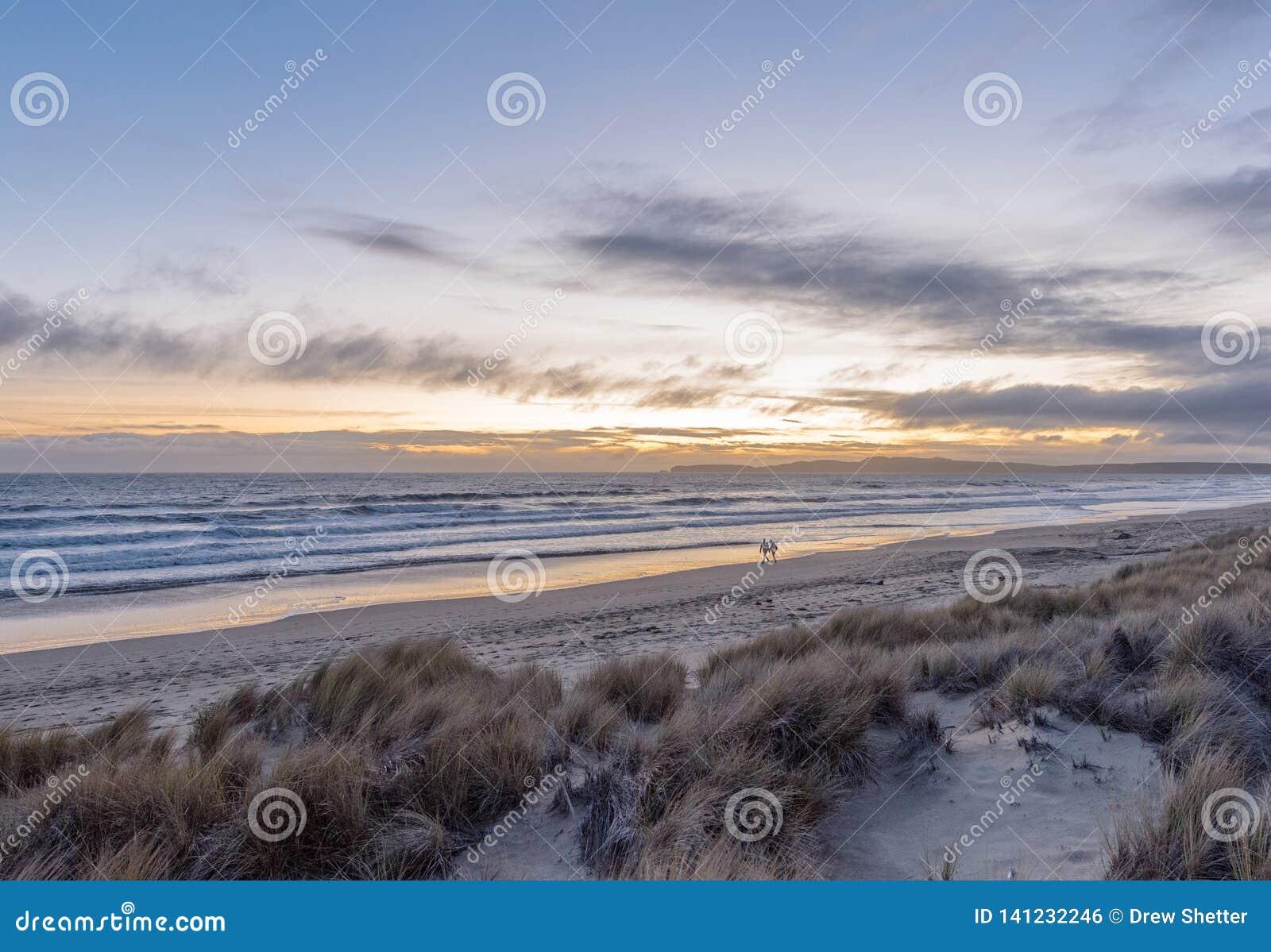 Pares en la distancia que camina a lo largo de la playa en la puesta del sol