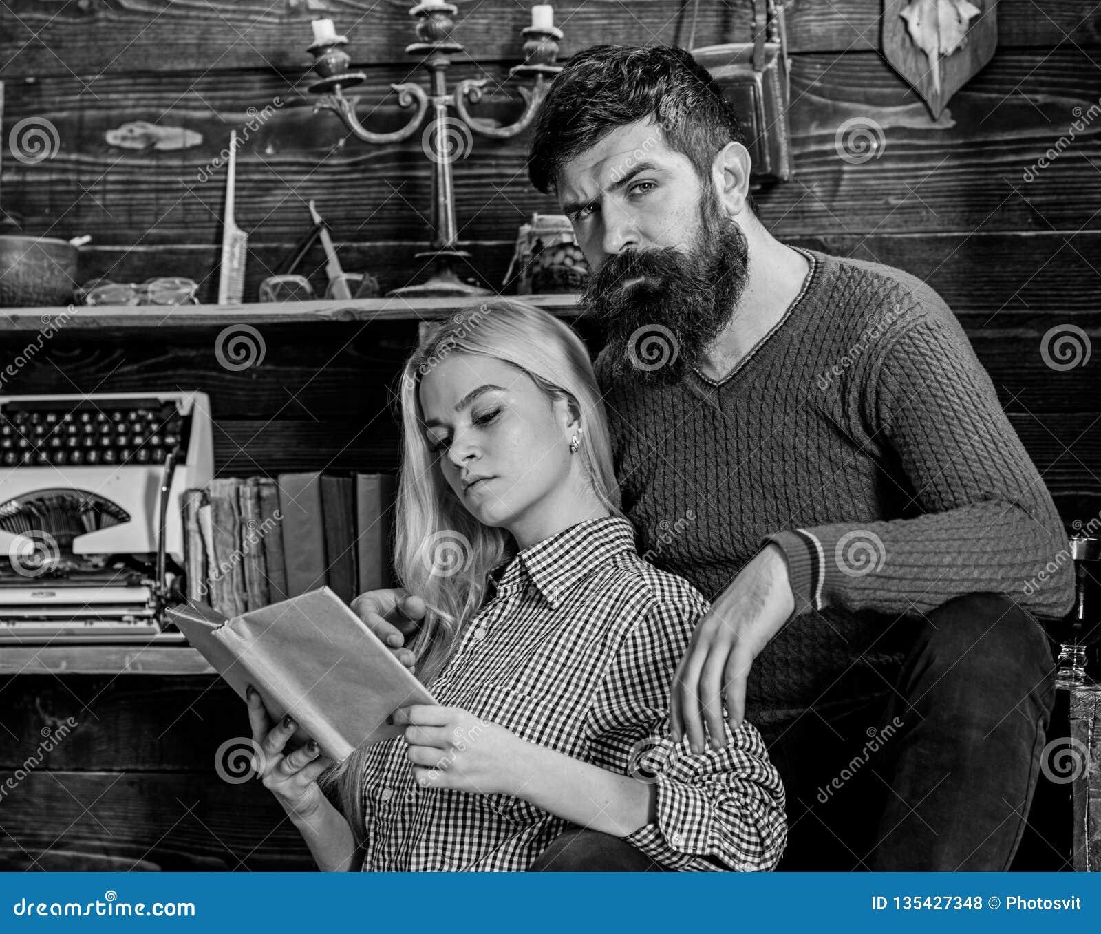 Pares en poesía de la lectura del amor en atmósfera caliente Señora y hombre con la barba en caras soñadoras con el libro, lectur