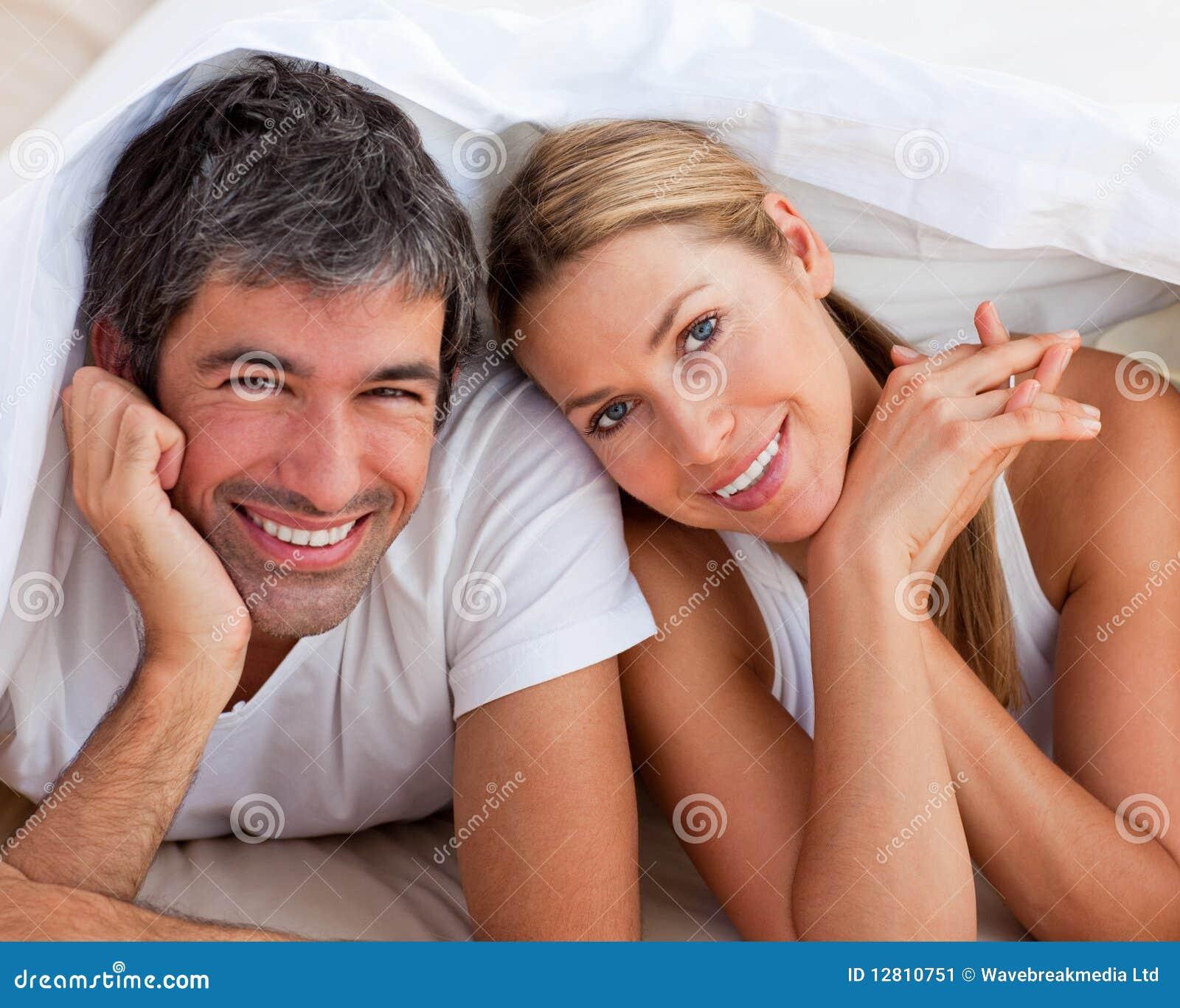 Pares Enamoured que têm o divertimento encontrar-se na cama