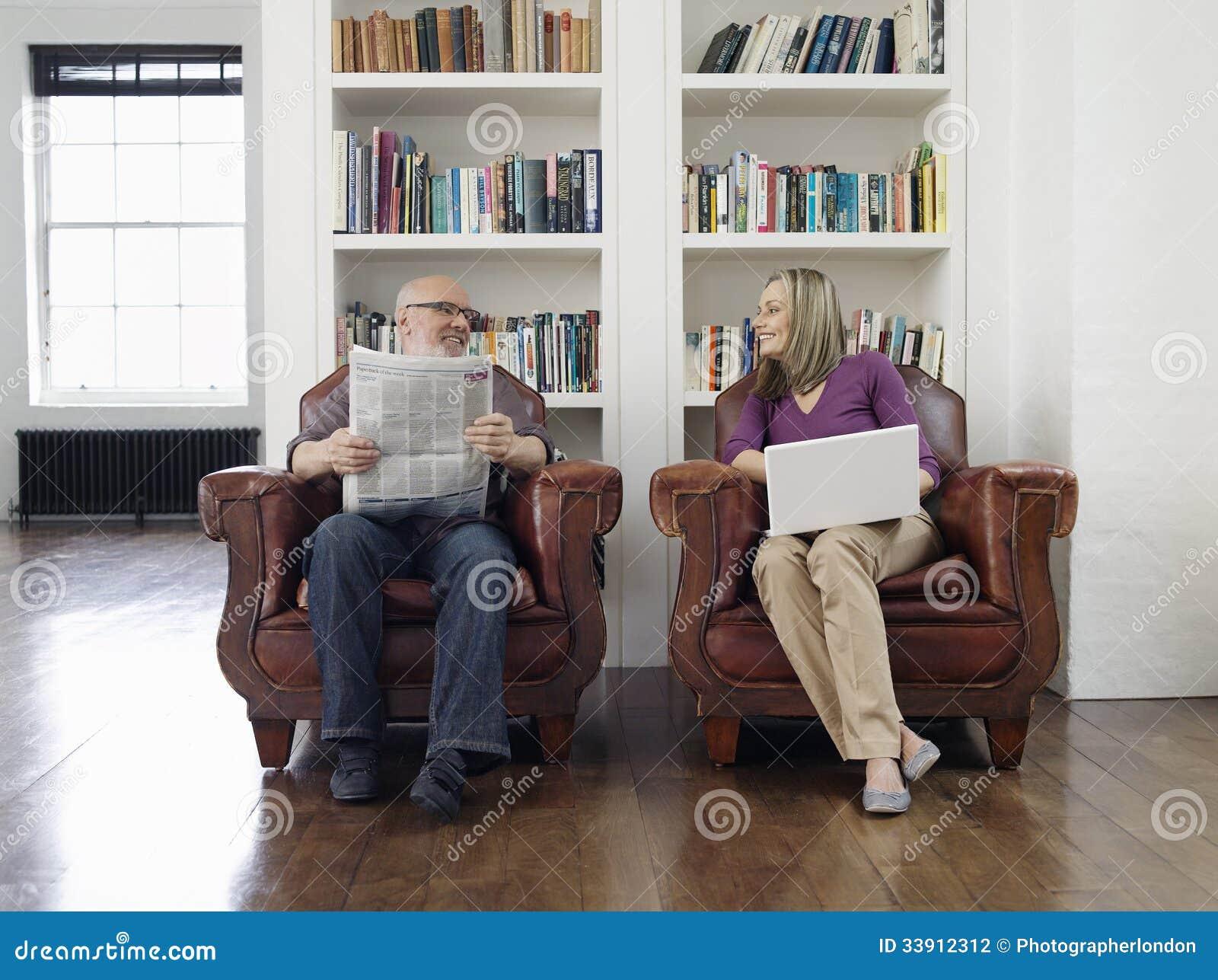 Pares envejecidos centro con el periódico y el ordenador portátil en casa