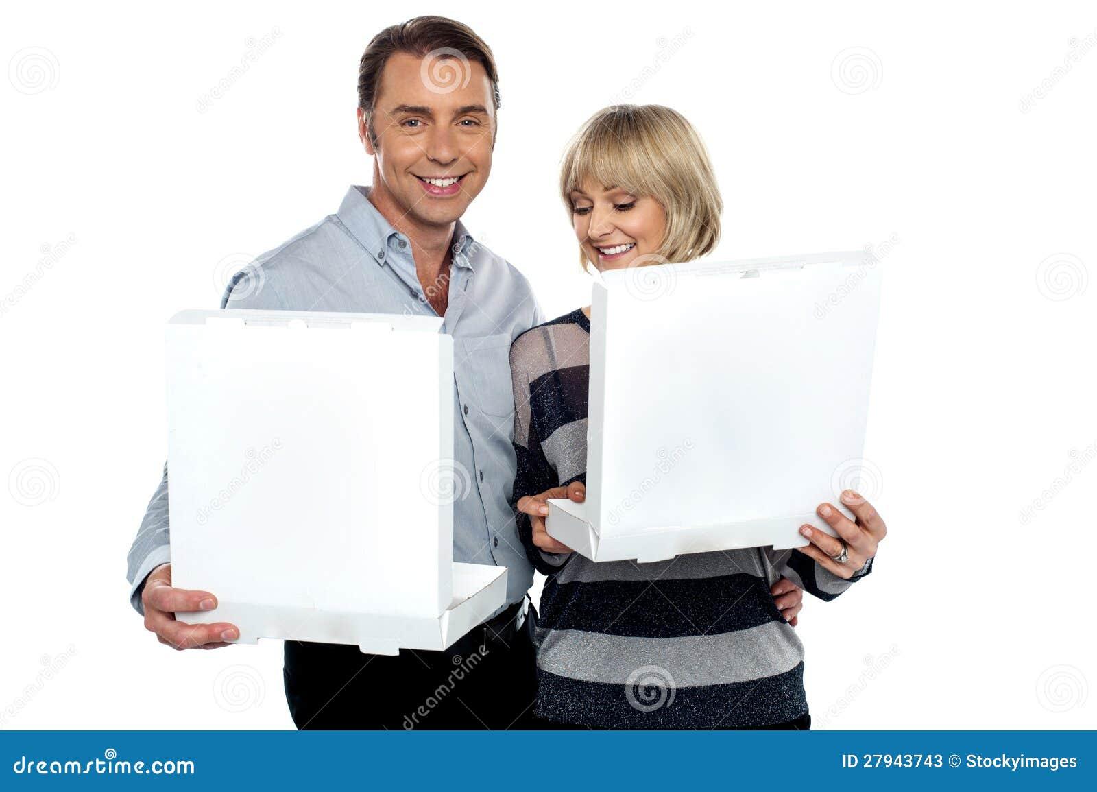 Pares envejecidos medios que sostienen los rectángulos blancos de la pizza