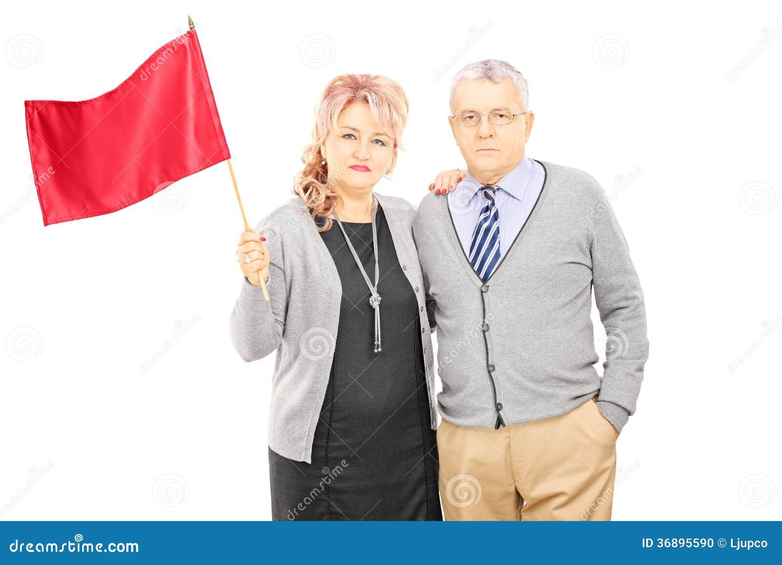 Pares envelhecidos meio que acenam uma bandeira vermelha