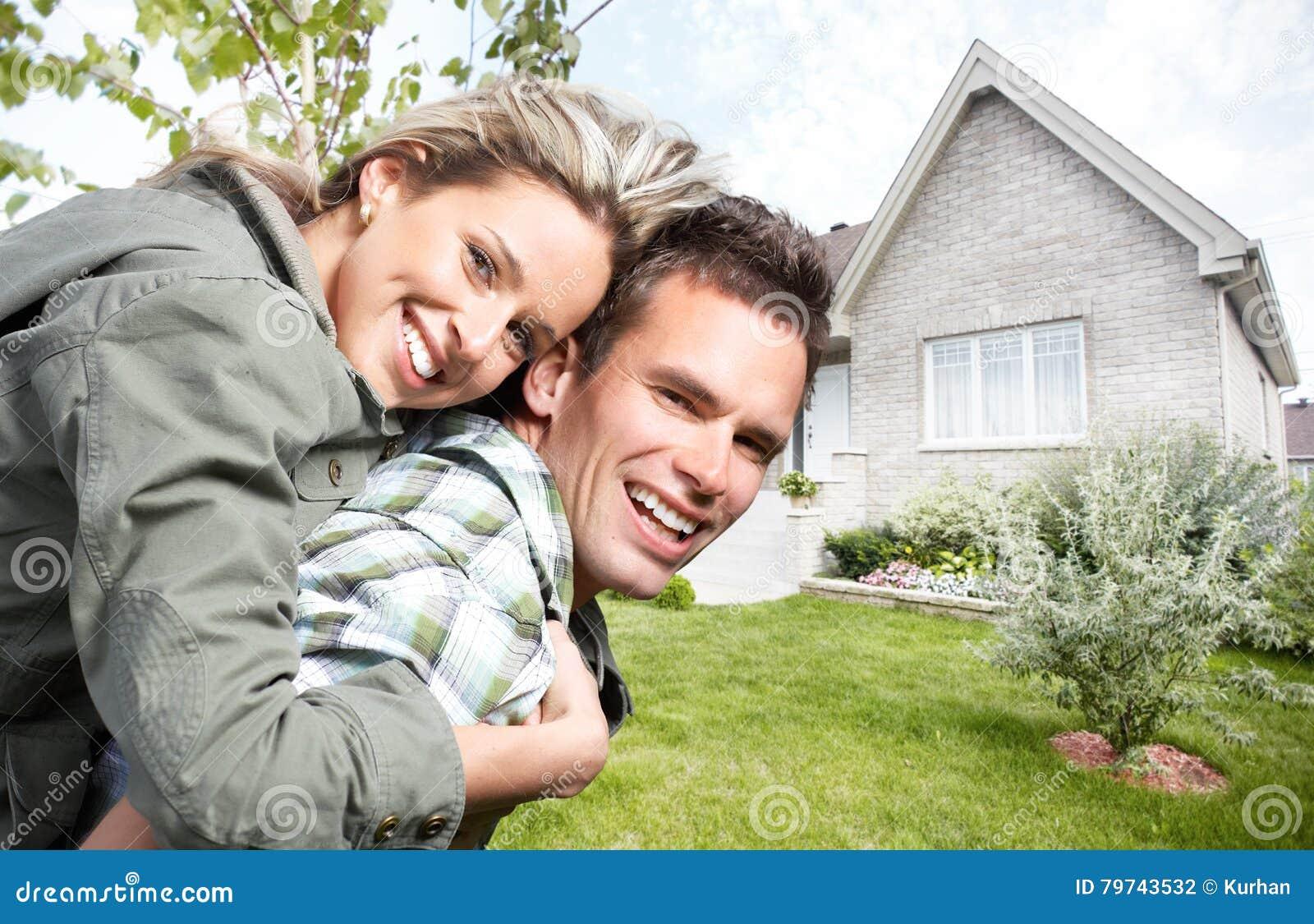 Pares felices cerca de la nueva casa