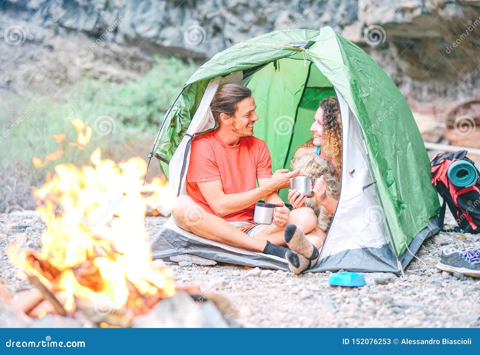 Pares felices de caminantes con su perro que acampa con la tienda alrededor de las montañas de la roca al lado del fuego - gente