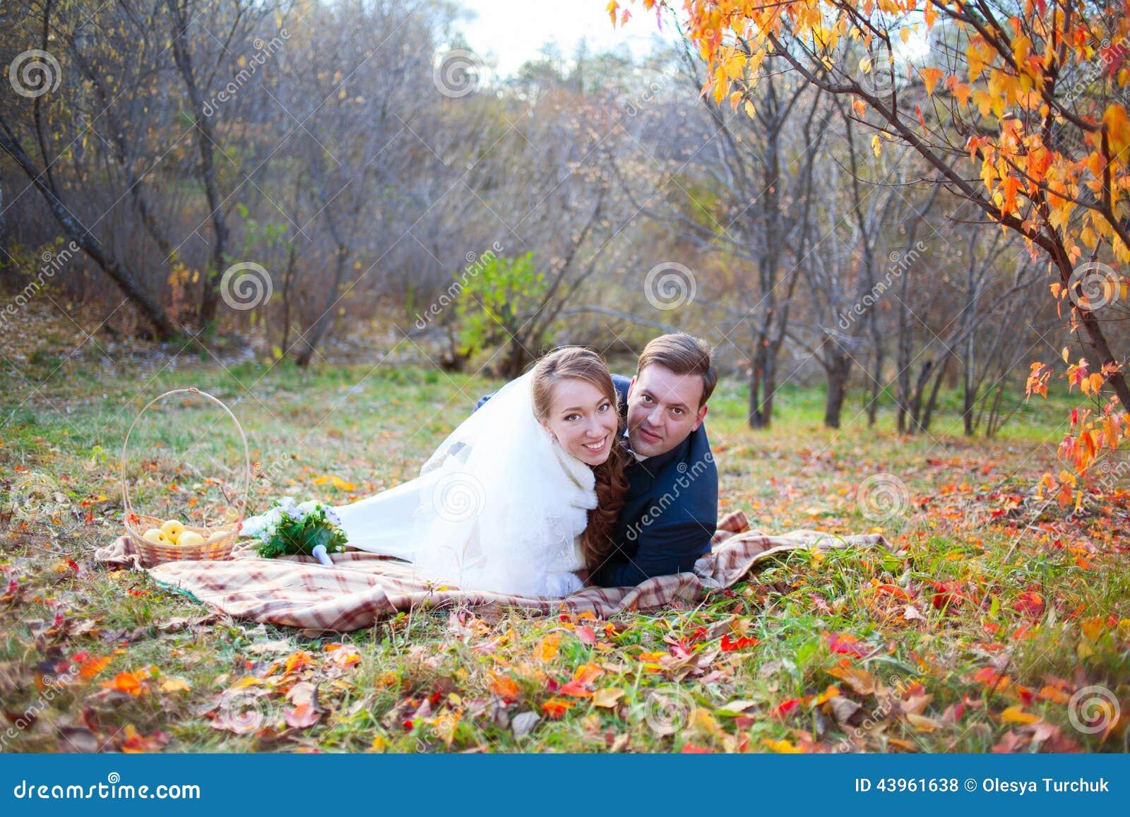 Pares felices de la boda en el bosque del invierno del otoño, mintiendo en abrazo de la tela escocesa
