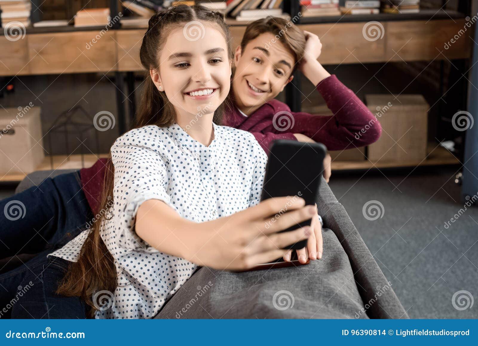 Pares felices del adolescente que toman el selfie en smartphone y que se sientan en el sofá en casa