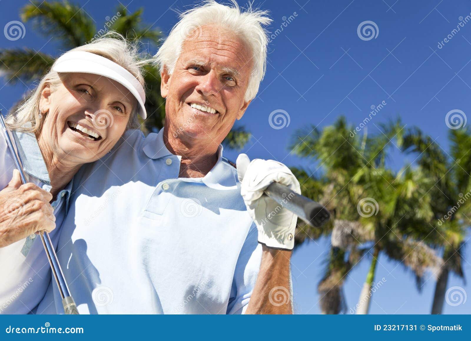 Pares felices del hombre mayor y de la mujer que juegan a golf