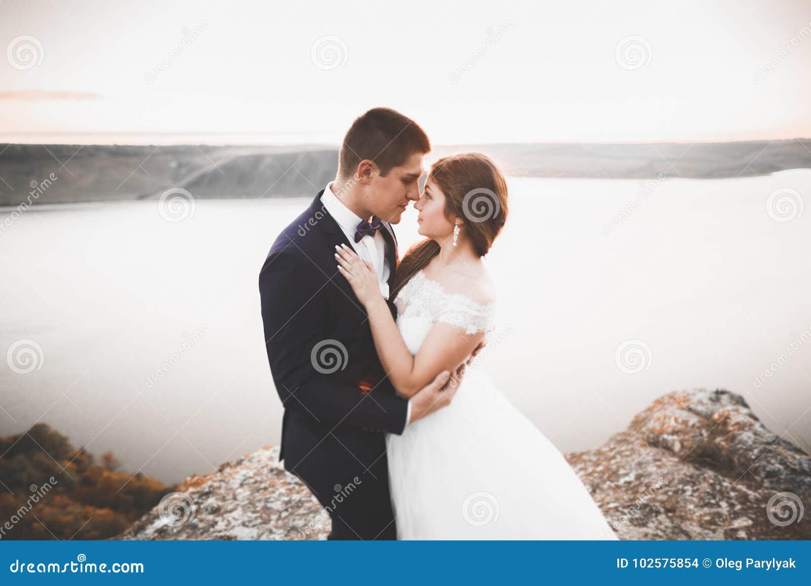 Pares felices elegantes elegantes de la boda, novia, novio magnífico en el fondo del mar y cielo