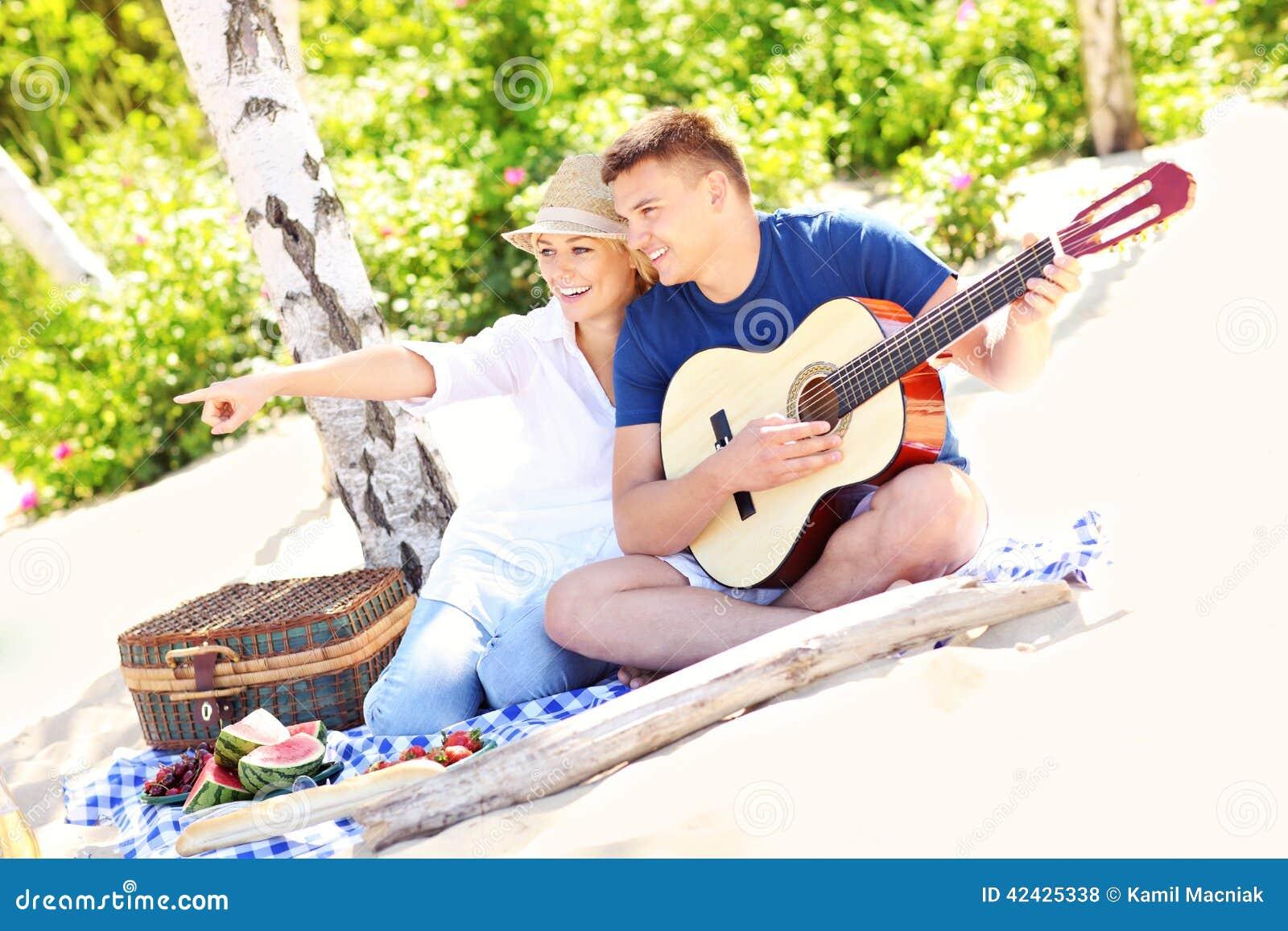 Pares felices en la playa con la guitarra