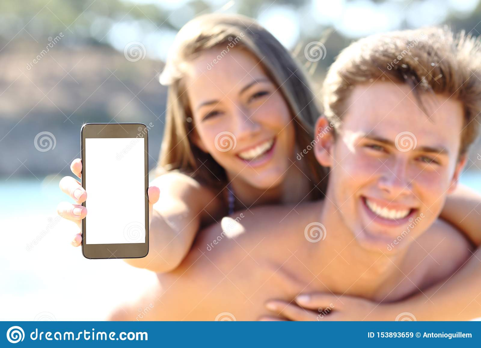 Pares felices en la playa que muestra la pantalla en blanco del teléfono