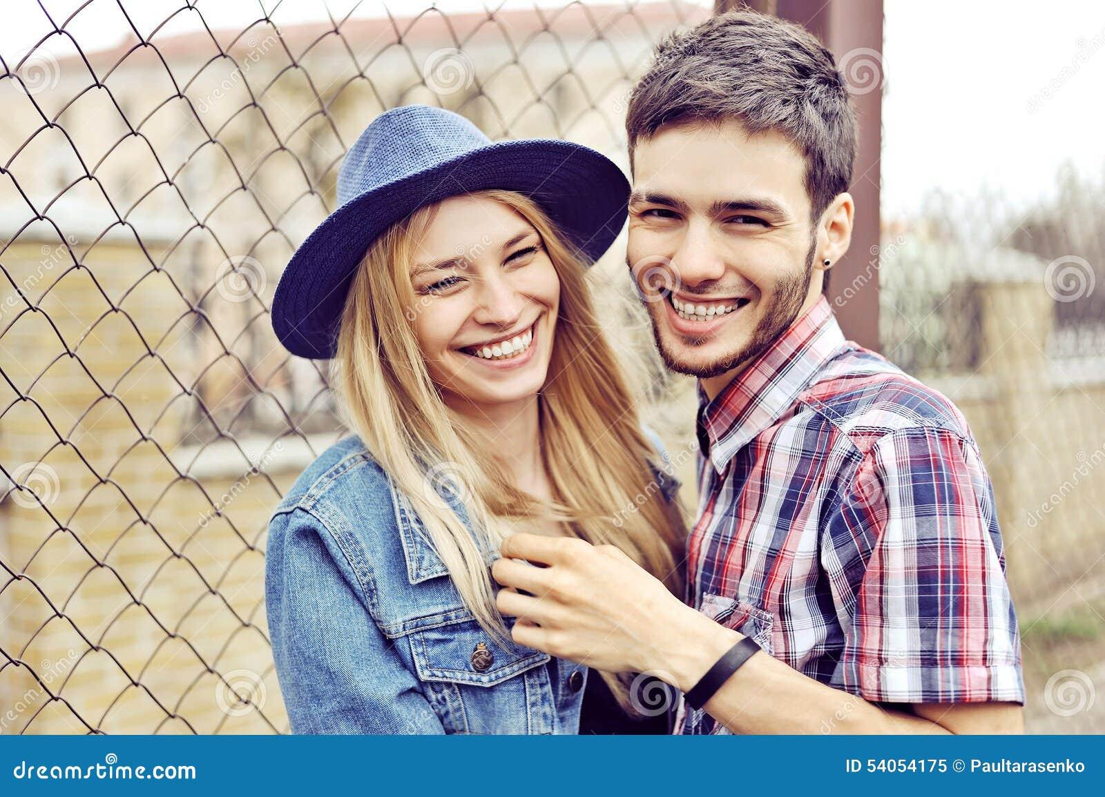 Pares felices jovenes que abrazan y que ríen