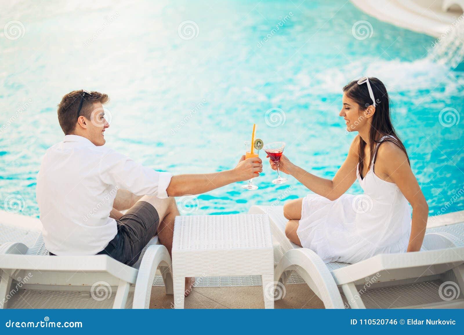 Pares felices positivos que tienen una tarde romántica por la piscina en centro turístico de vacaciones de lujo de verano Coctele