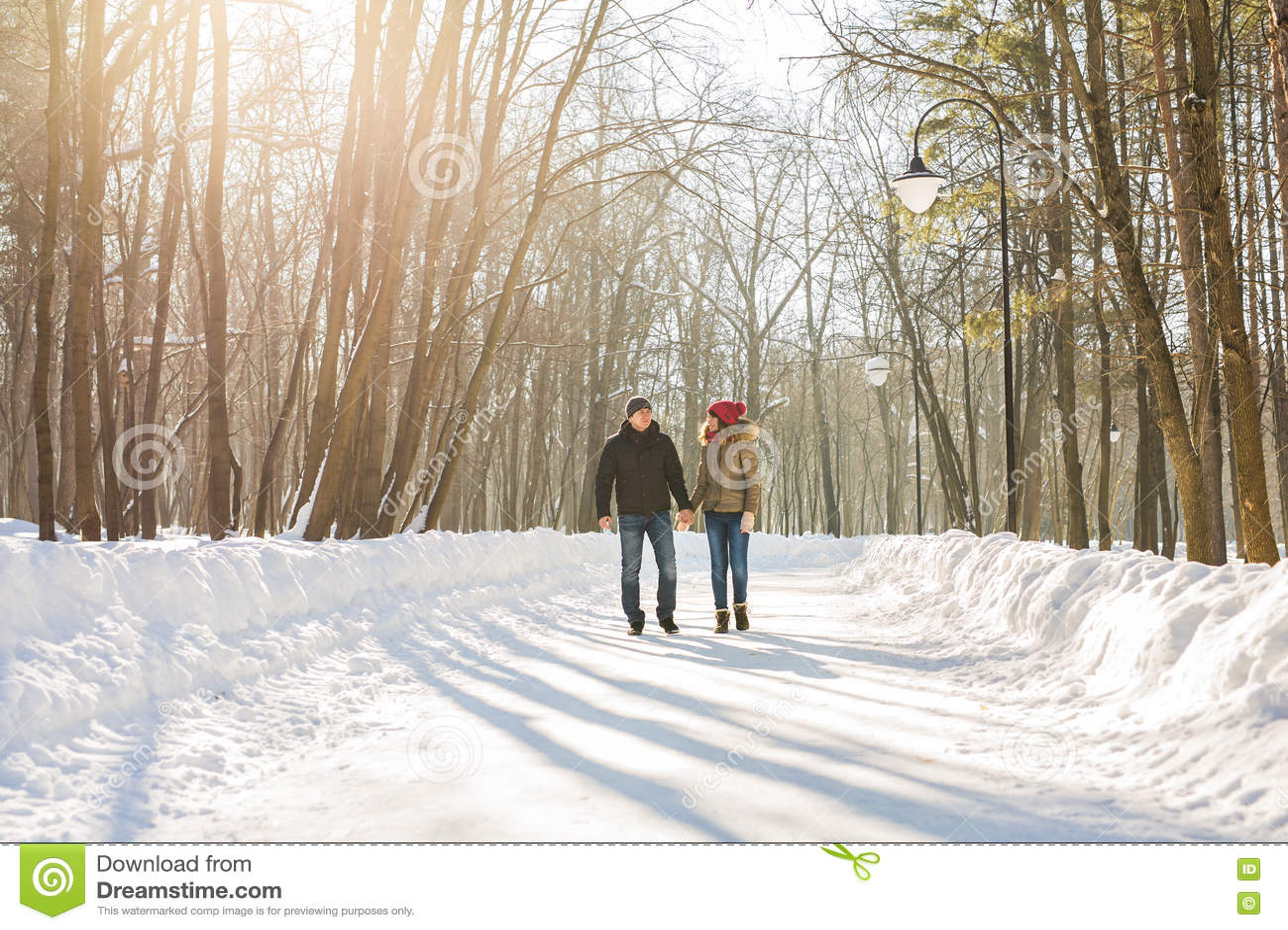 Pares felices que caminan a través de un bosque nevoso en invierno