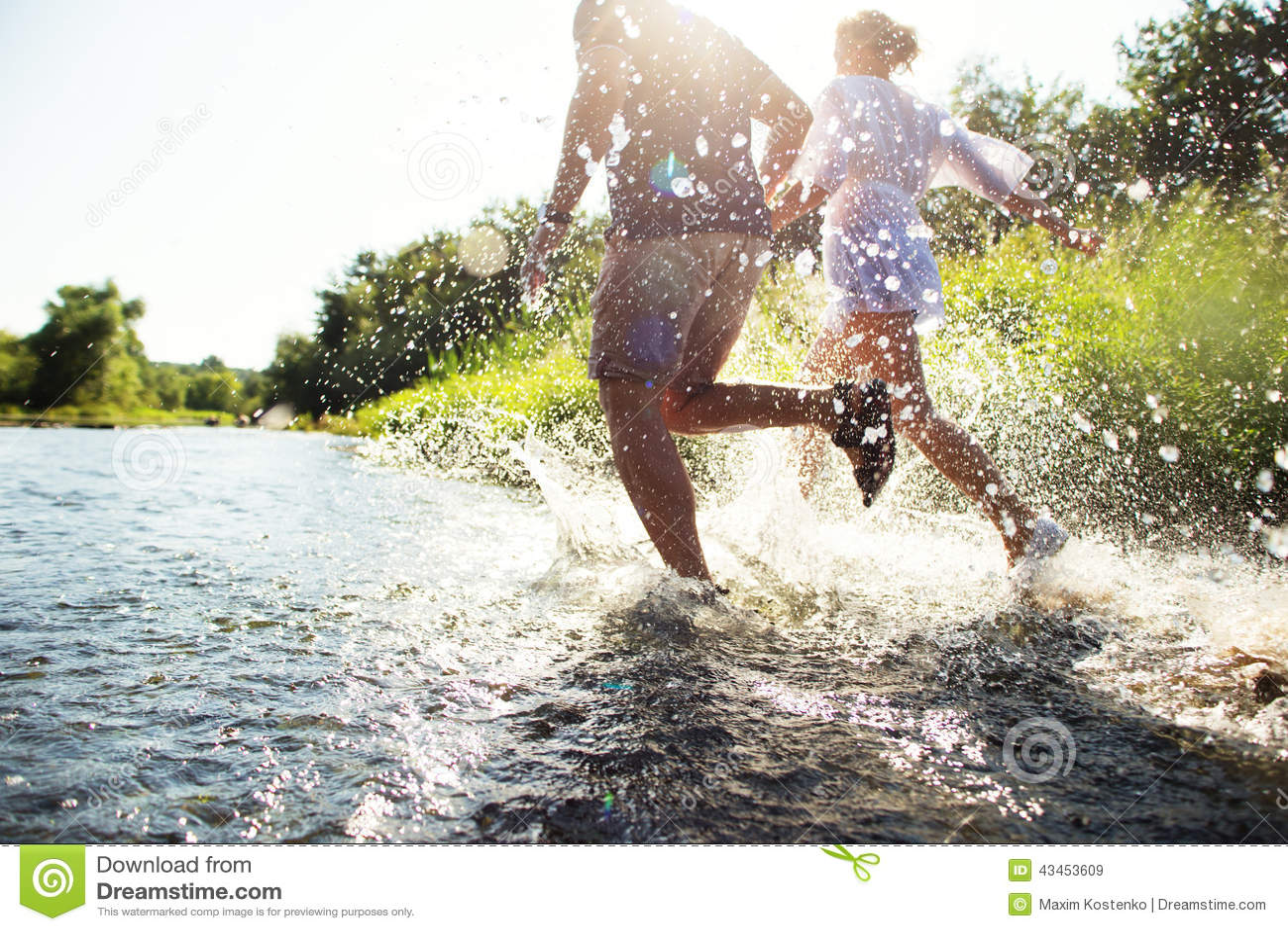 Pares felices que corren en agua poco profunda