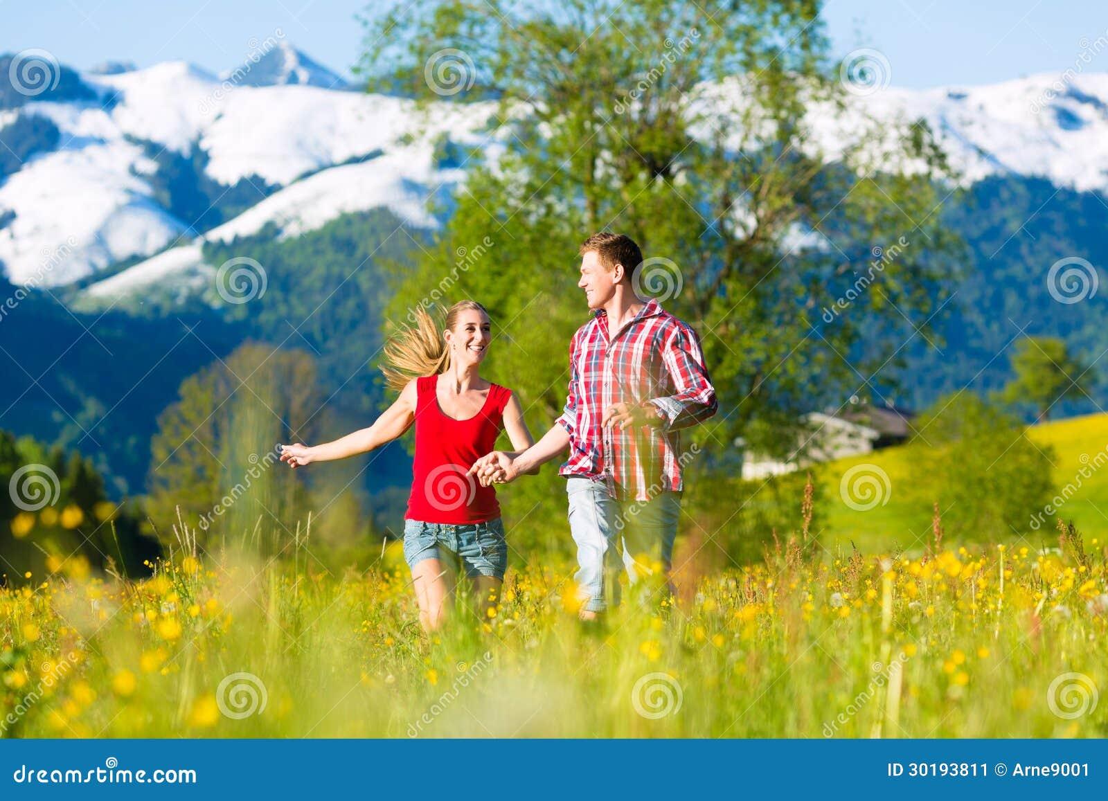 Pares que corren en el prado con la montaña