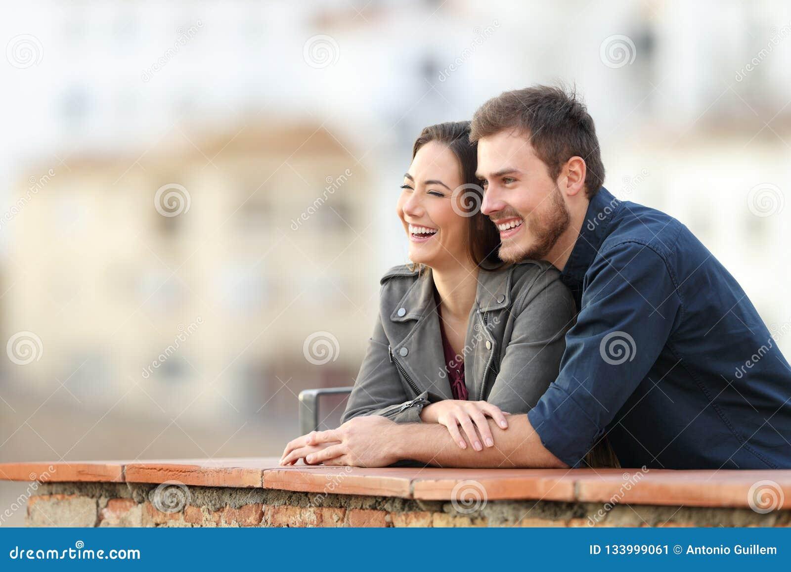 Pares felices que disfrutan de opiniones en una terraza de vacaciones