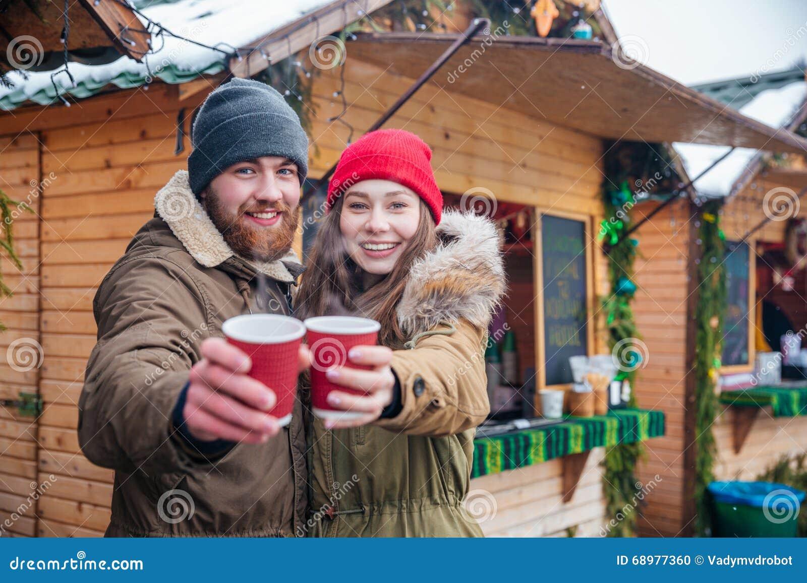 Pares felices que le ofrecen bebidas calientes en mercado de la Navidad