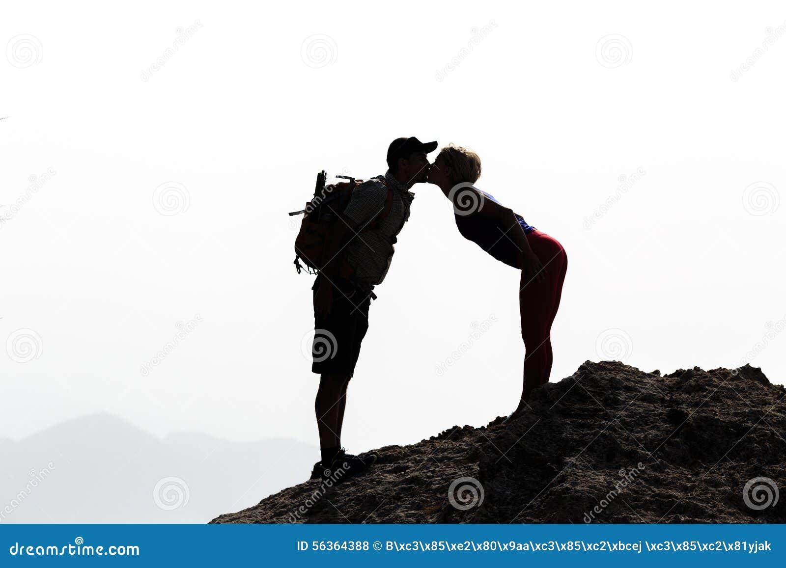 Pares felices que se besan en cumbre de la montaña
