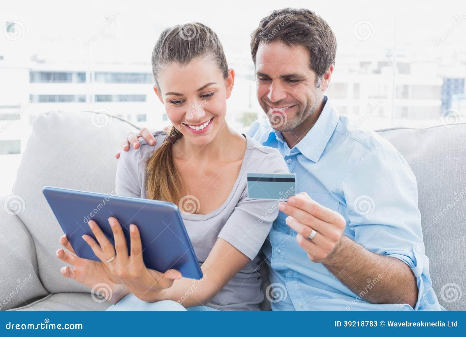 Pares felices que se relajan en el sofá que hace compras en línea con PC de la tableta