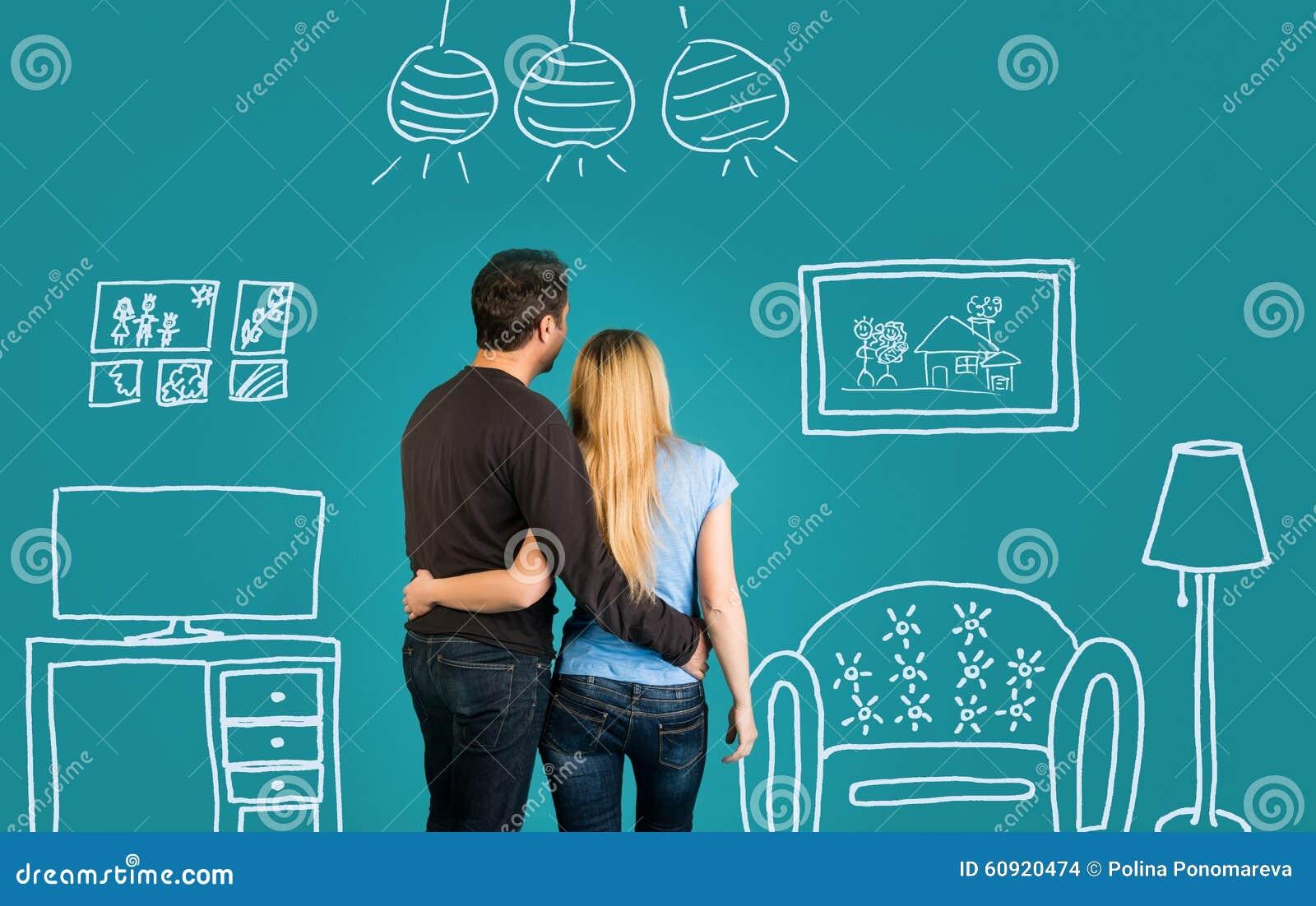 Pares felices que sueñan con su nuevo hogar o que suministran en fondo azul Familia con el dibujo de bosquejo de su interior plan