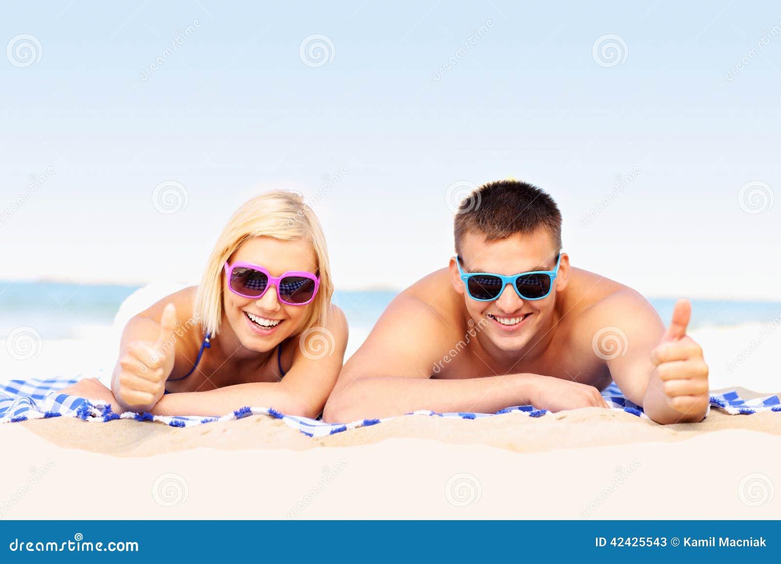Pares felices que toman el sol en la playa