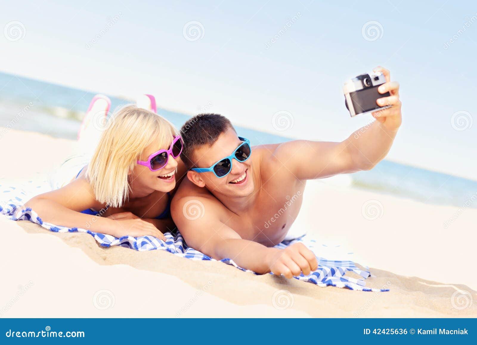 Pares felices que toman imágenes en la playa