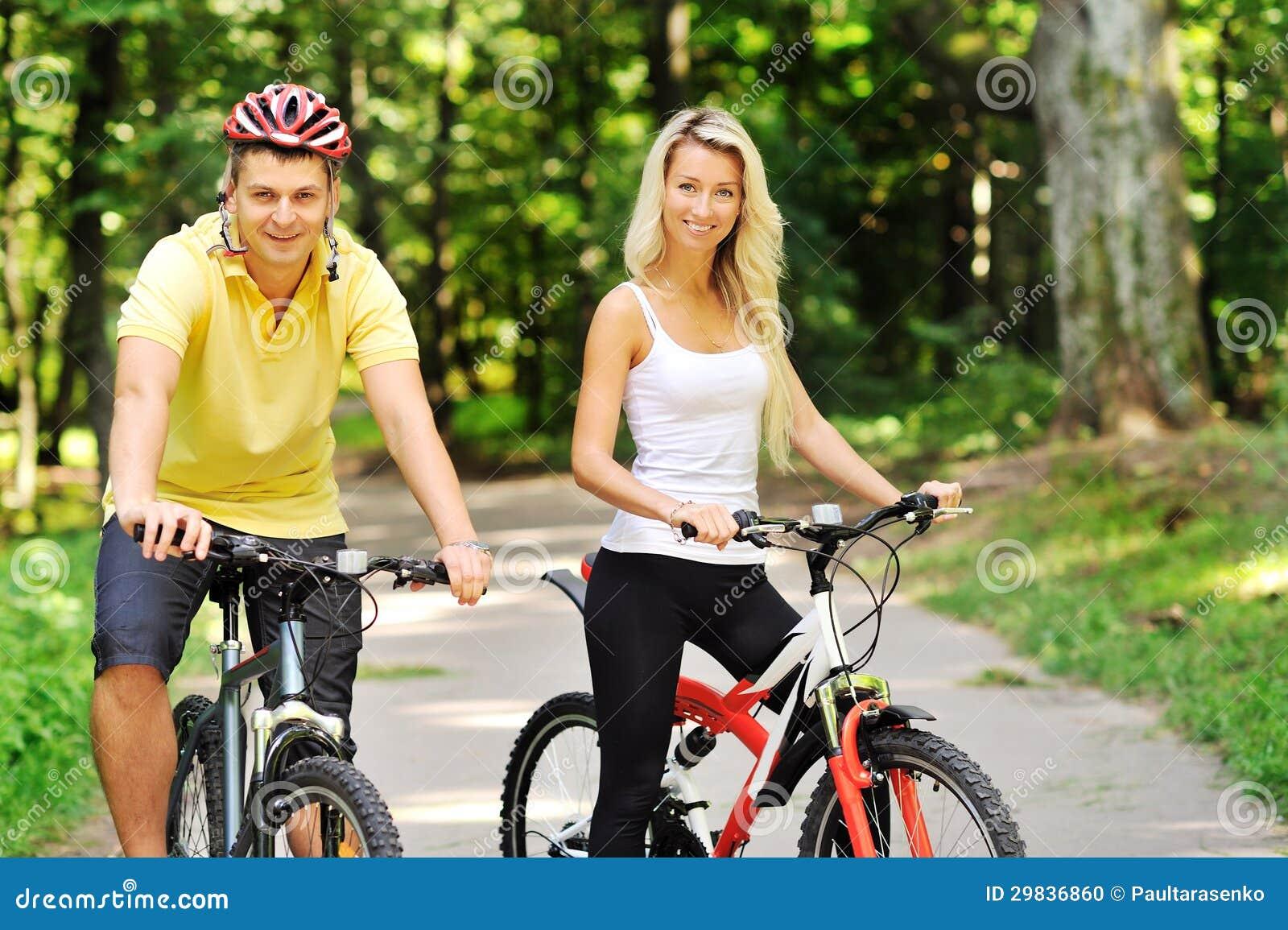 Pares felizes atrativos no bicicletas em um campo