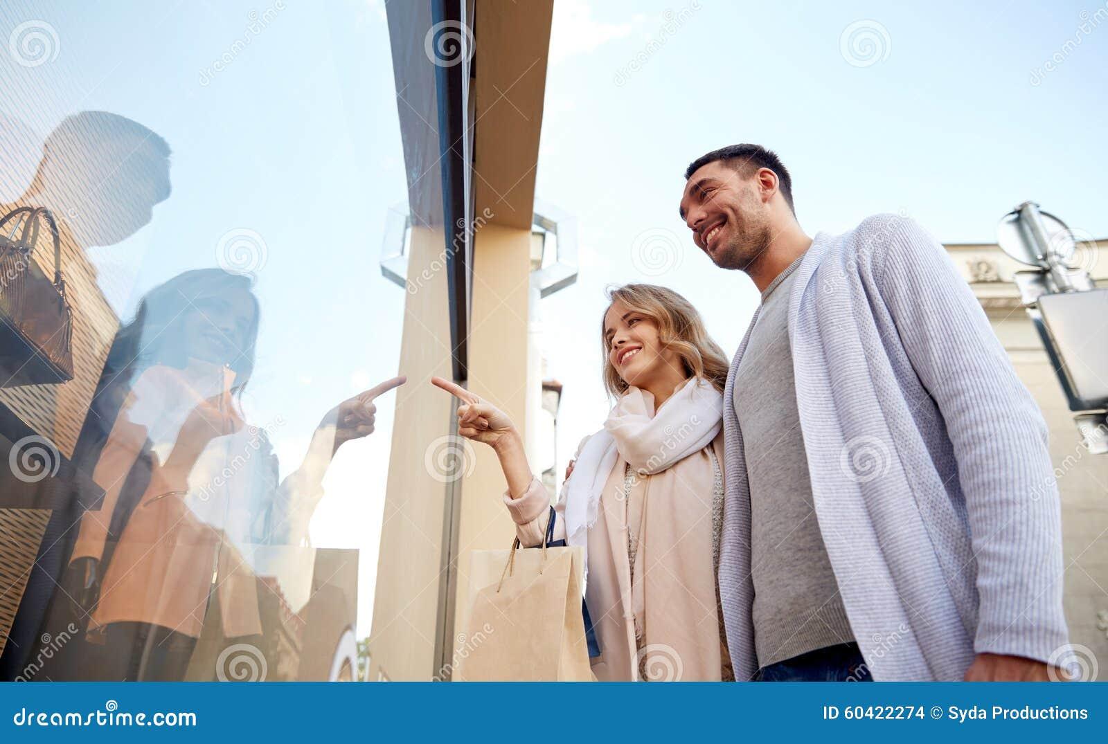 Pares felizes com os sacos de compras na janela da loja