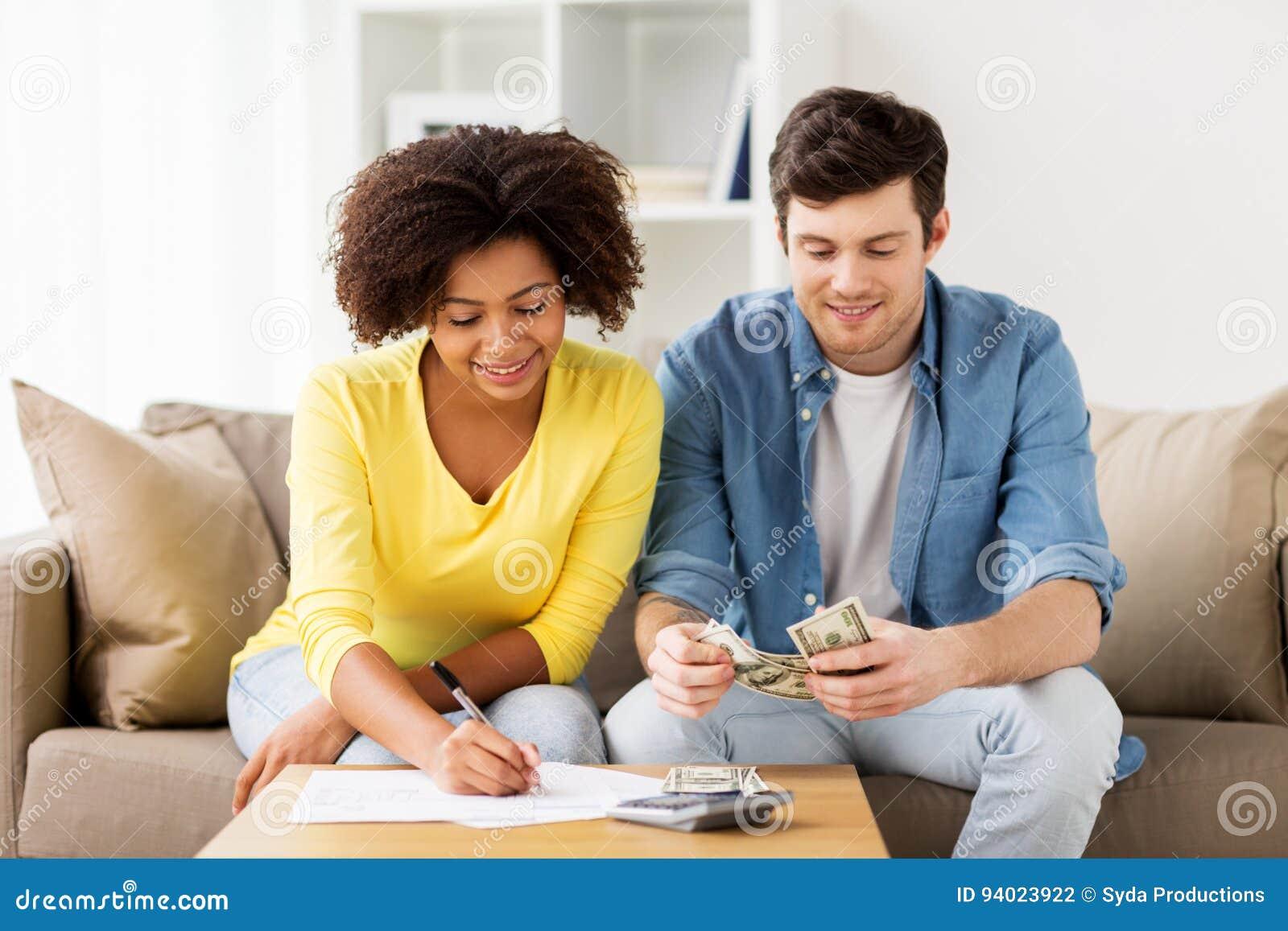 Pares felizes com papéis e calculadora em casa