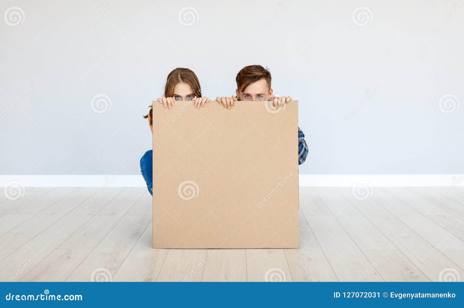 Pares felizes da família com o cartaz do cartão na parede vazia