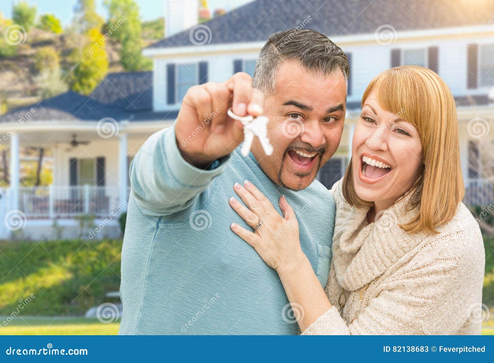 Pares felizes da raça misturada na frente da casa com chaves novas