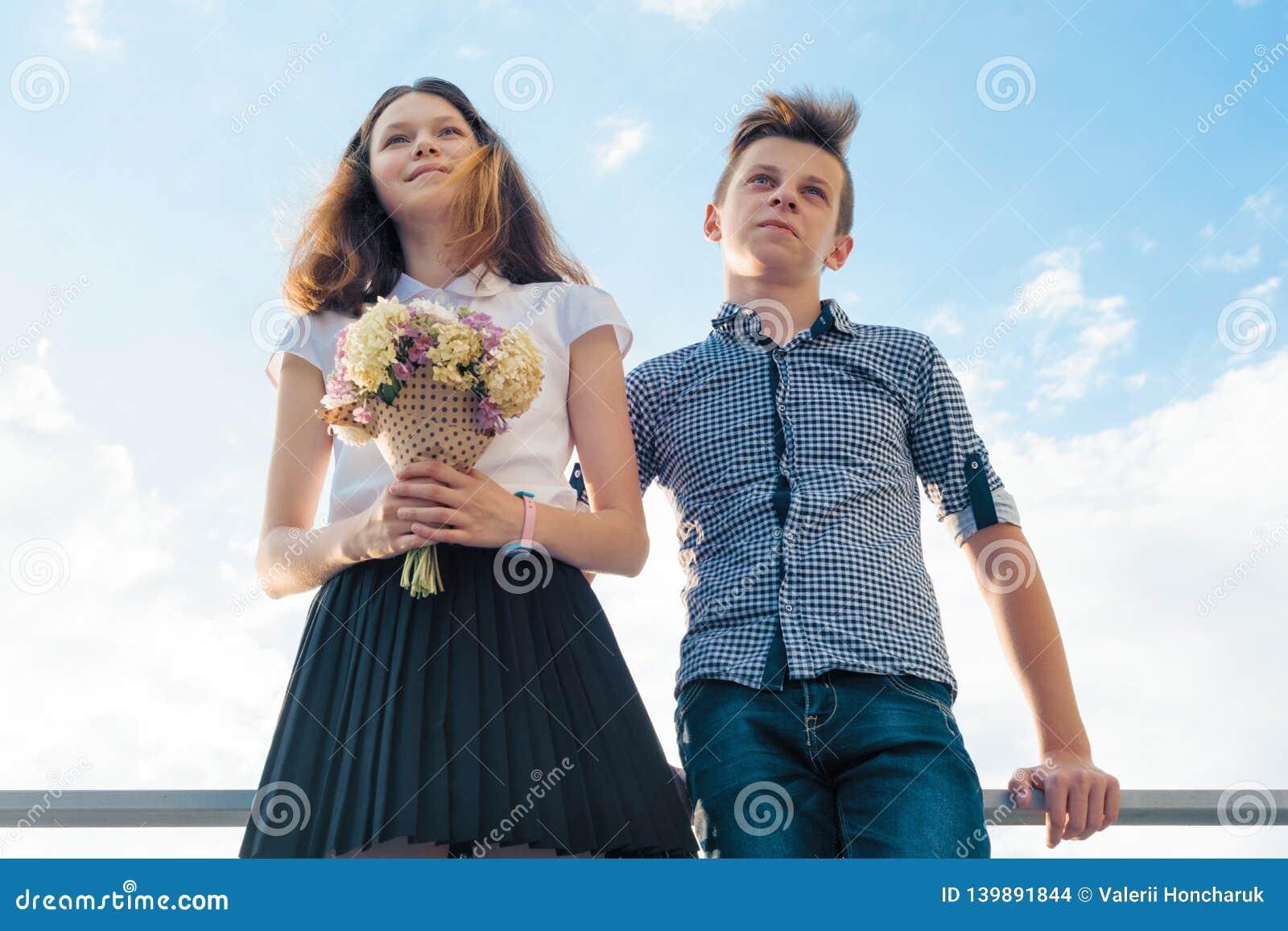 Pares felizes de adolescentes menino e de menina 14, 15 anos velhos Jovens que sorriem e que falam, fundo do céu azul