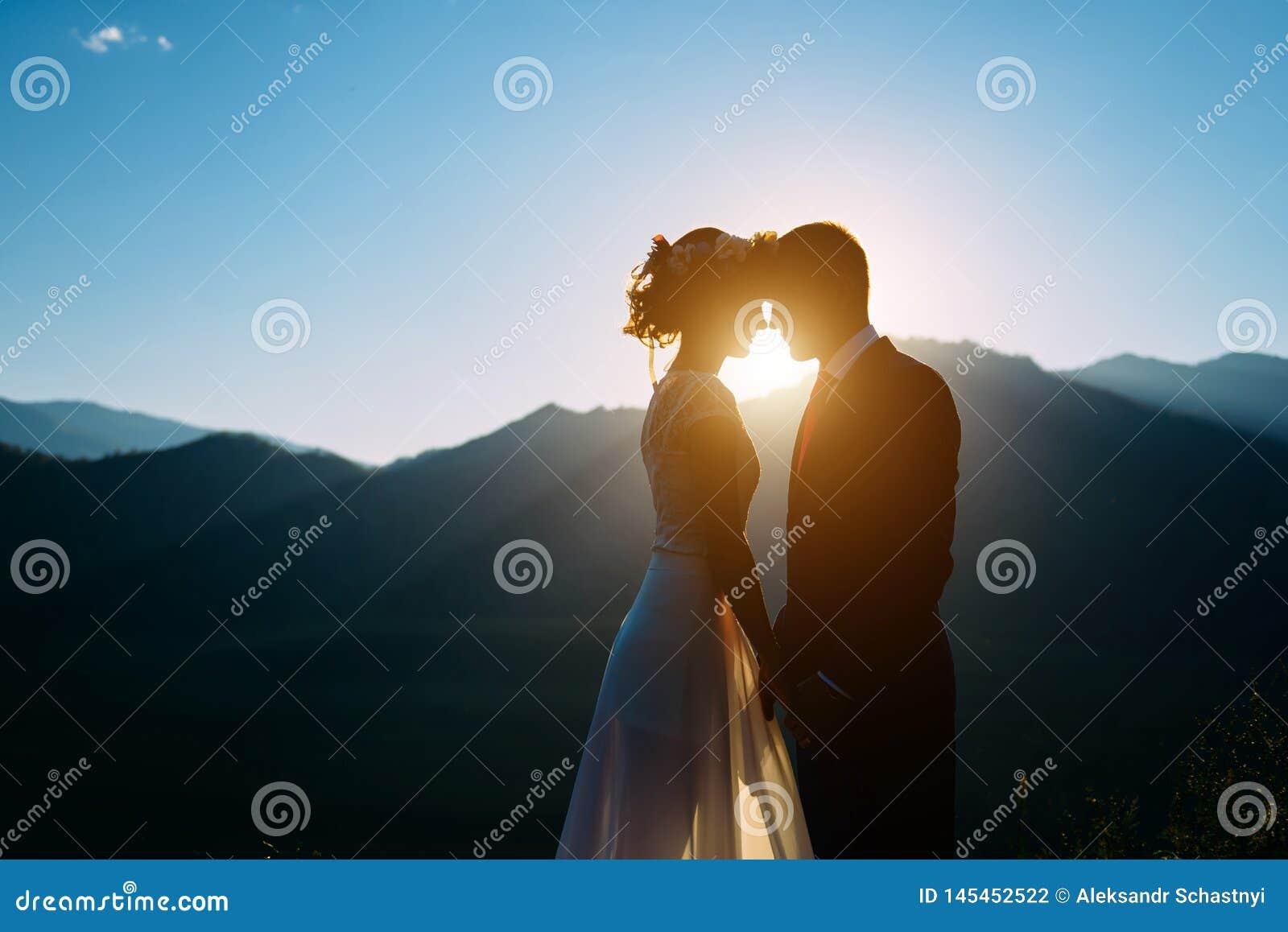 Pares felizes do casamento que ficam e que beijam sobre a paisagem bonita com montanhas
