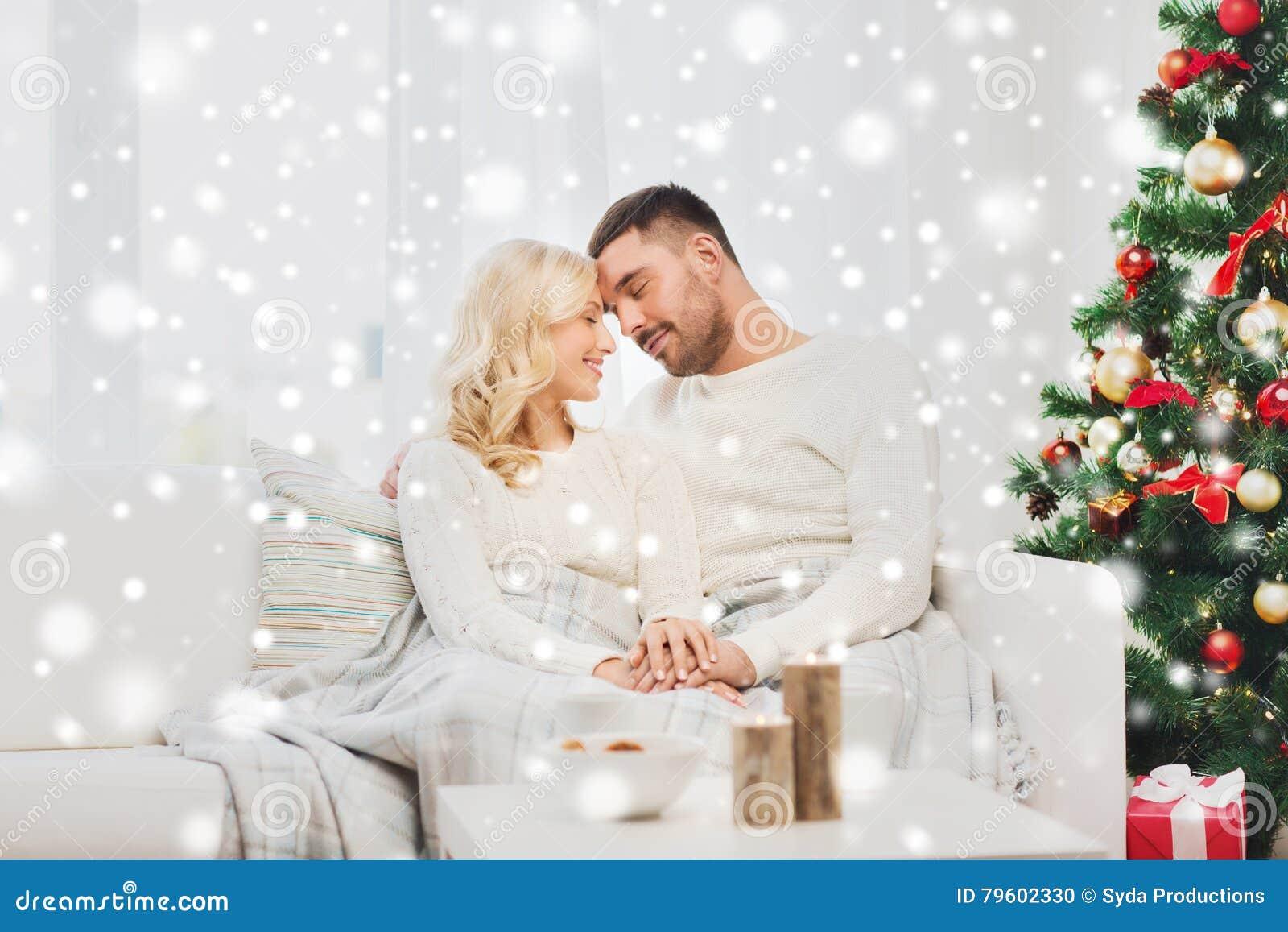 Pares felizes em casa com árvore de Natal