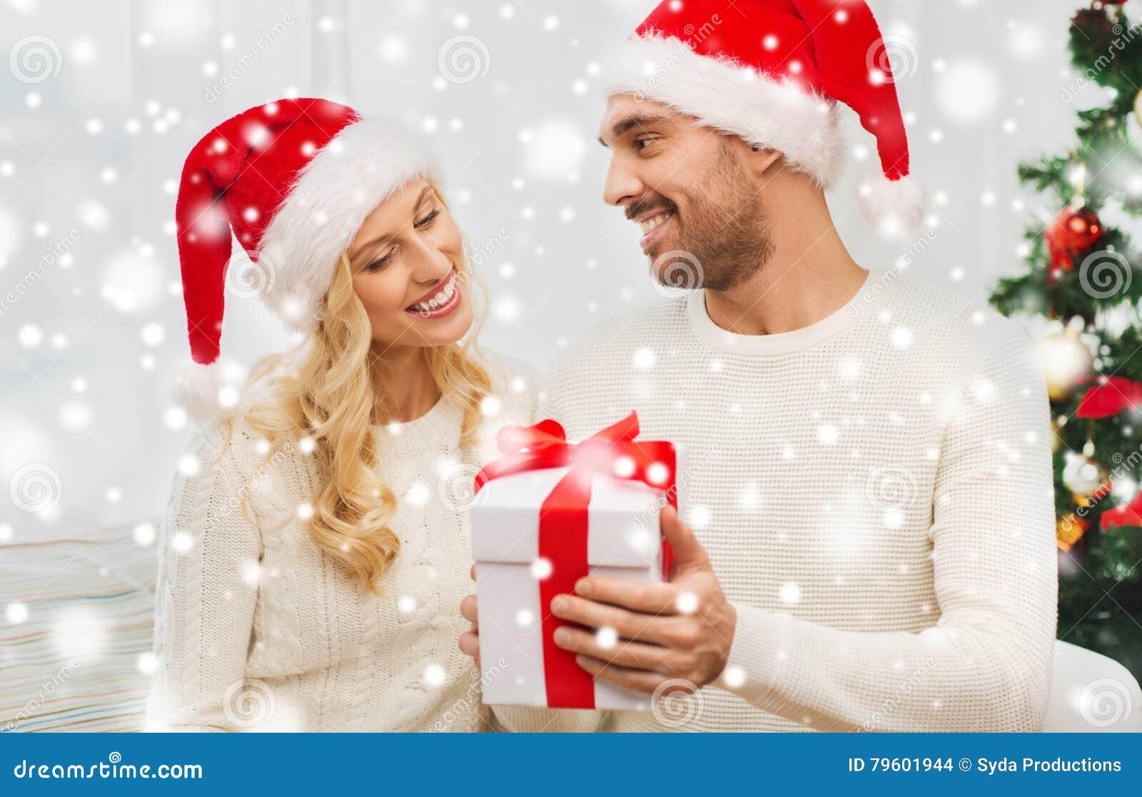Pares felizes em casa com caixa de presente do Natal